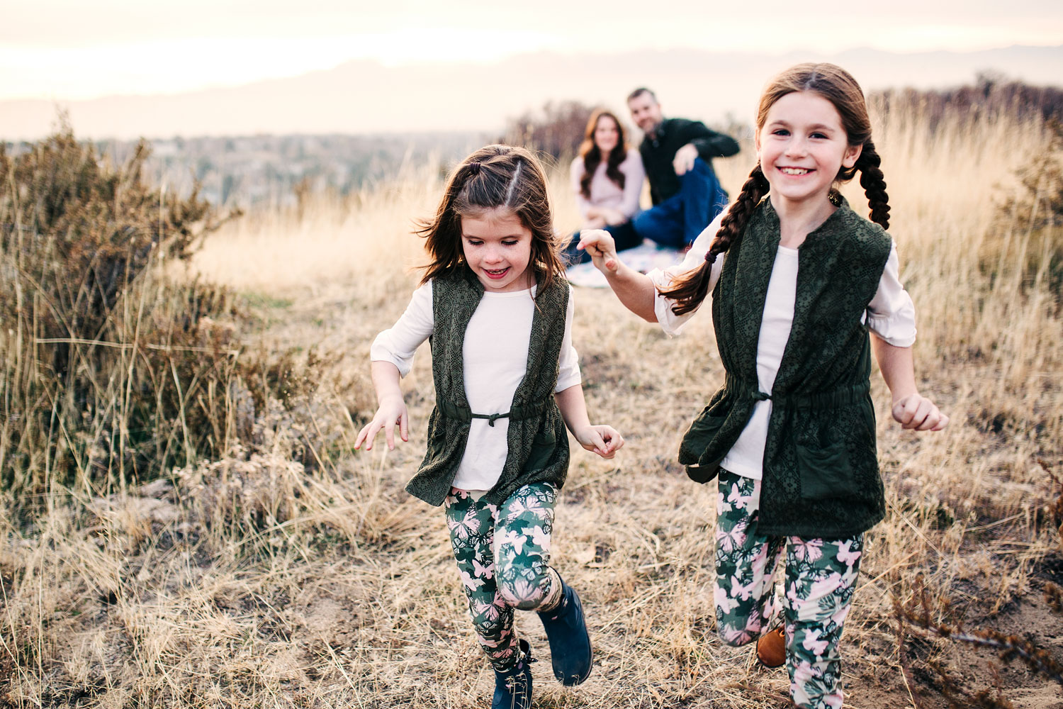 Two girls run and play during a fun family photo session with Amy Wright Photography in Roseville, California.