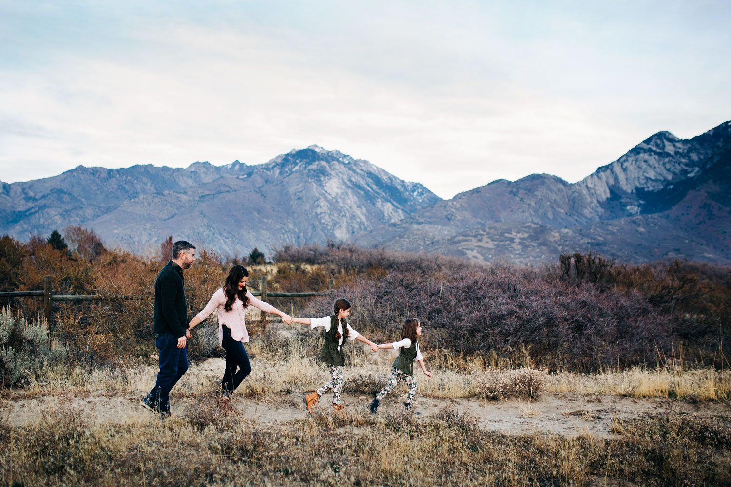 A family of four is walking together and holding hands during a photo session with Amy Wright, who is a photographer based out of Sacramento, California.
