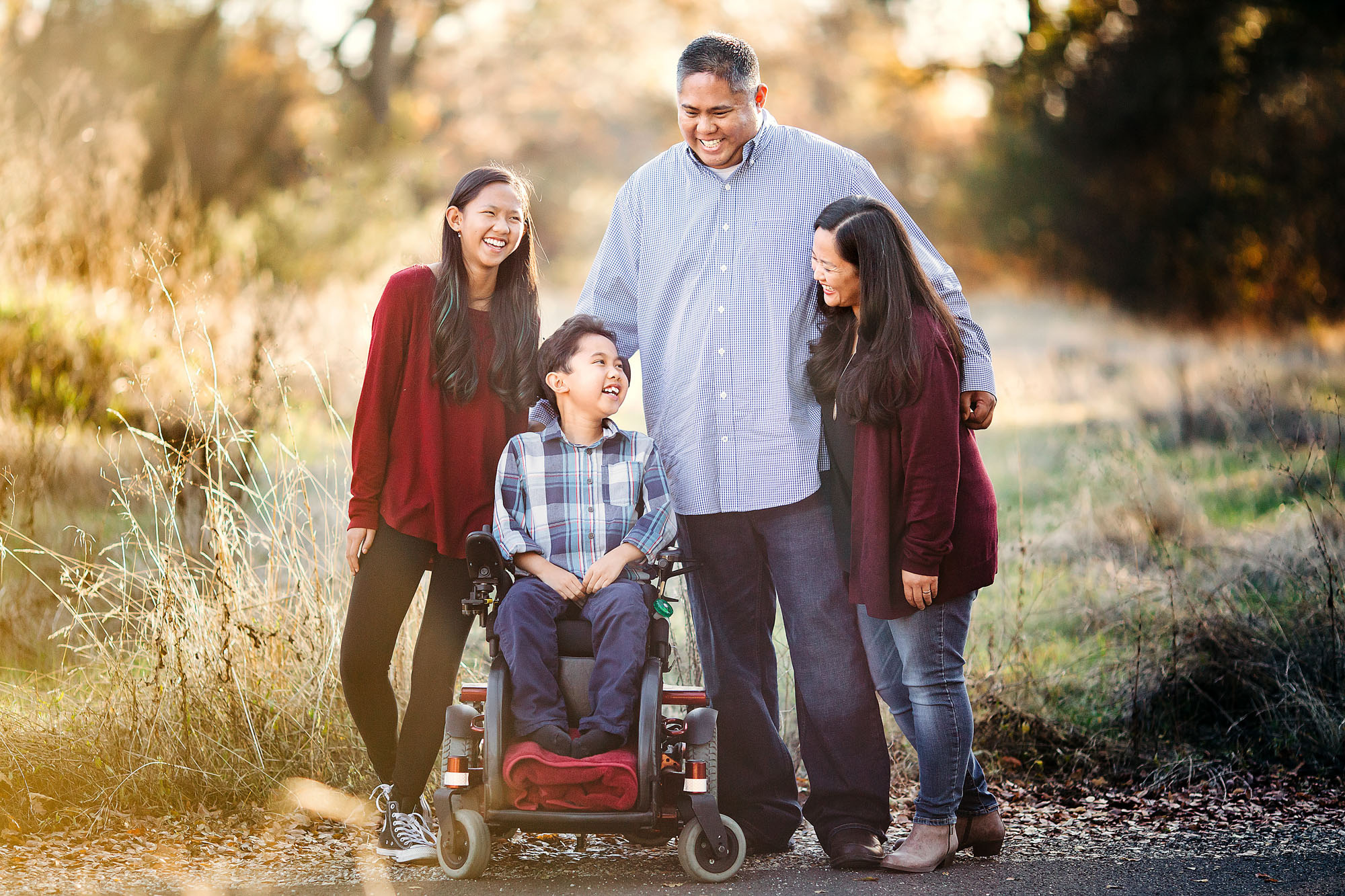 A family of four laughs together during a lifestyle photo session with photographer Amy Wright in Roseville, California.