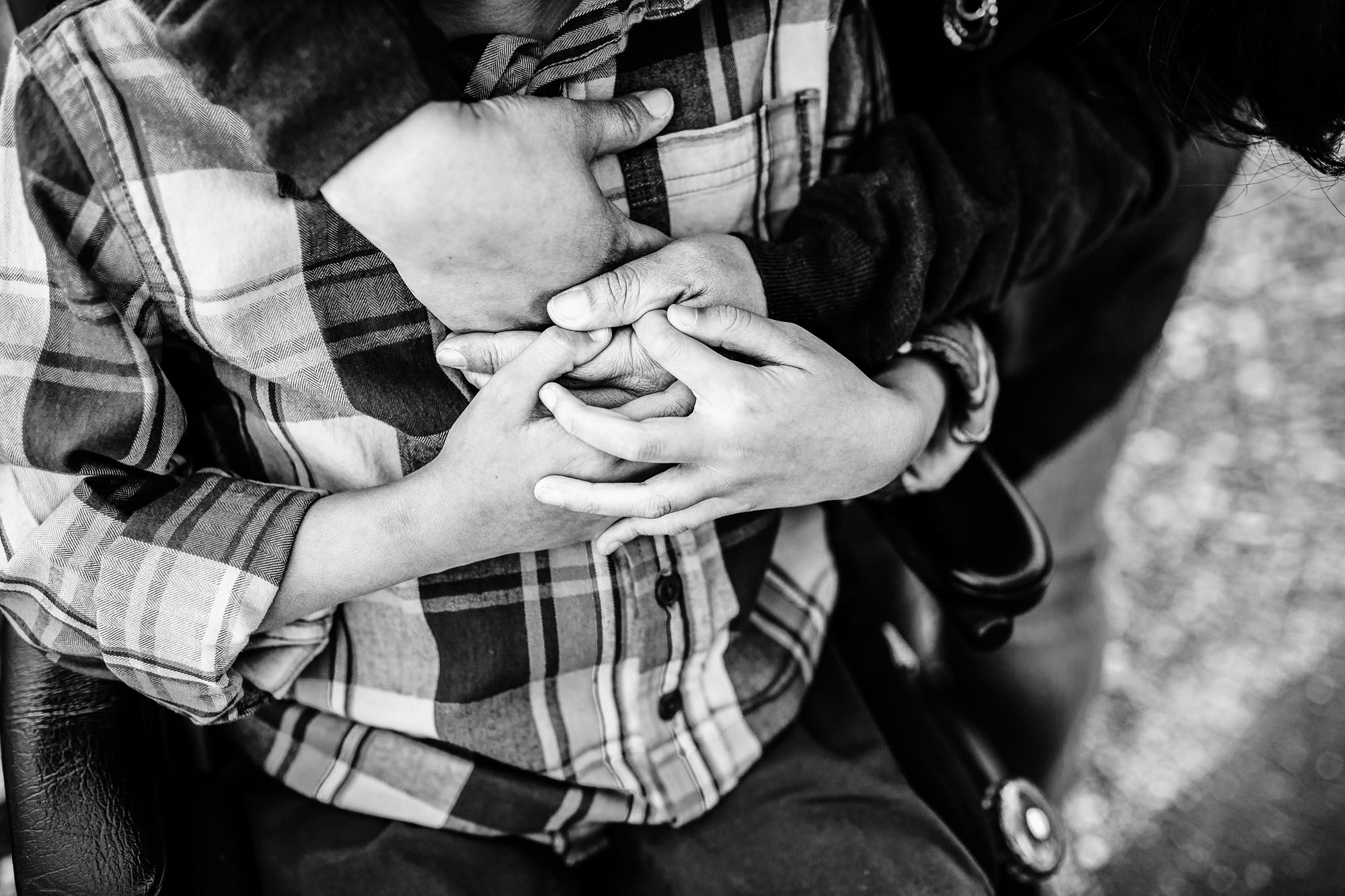 A mother and son grasp hands in a detail black and white photo taken by Amy Wright, a photographer based out of Roseville, California.