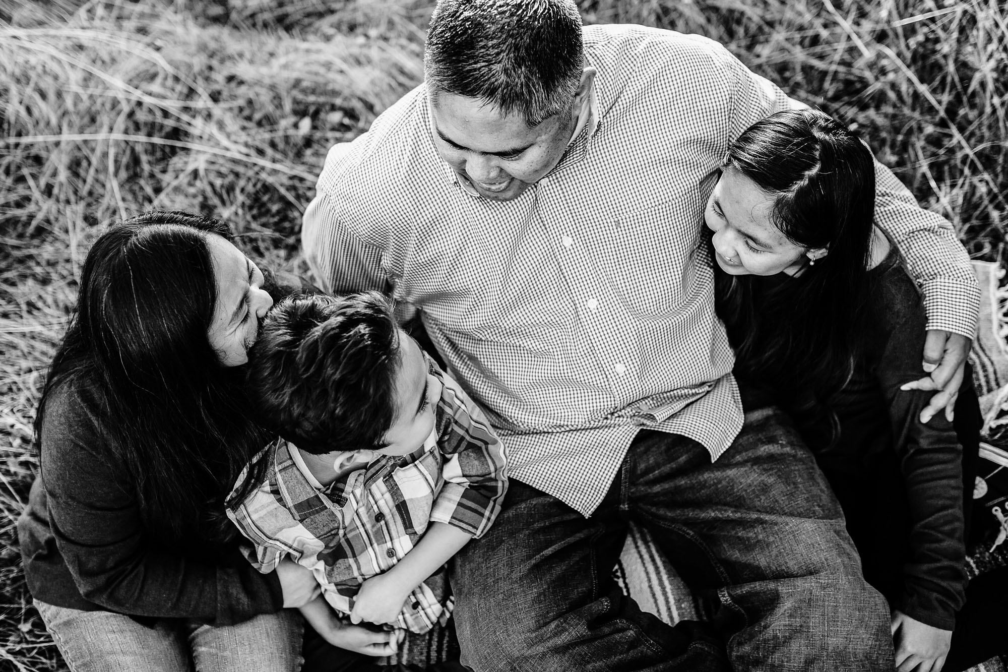 A family of four wrap their arms around each other during a lifestyle photo shoot in Roseville, California with Amy Wright Photography.