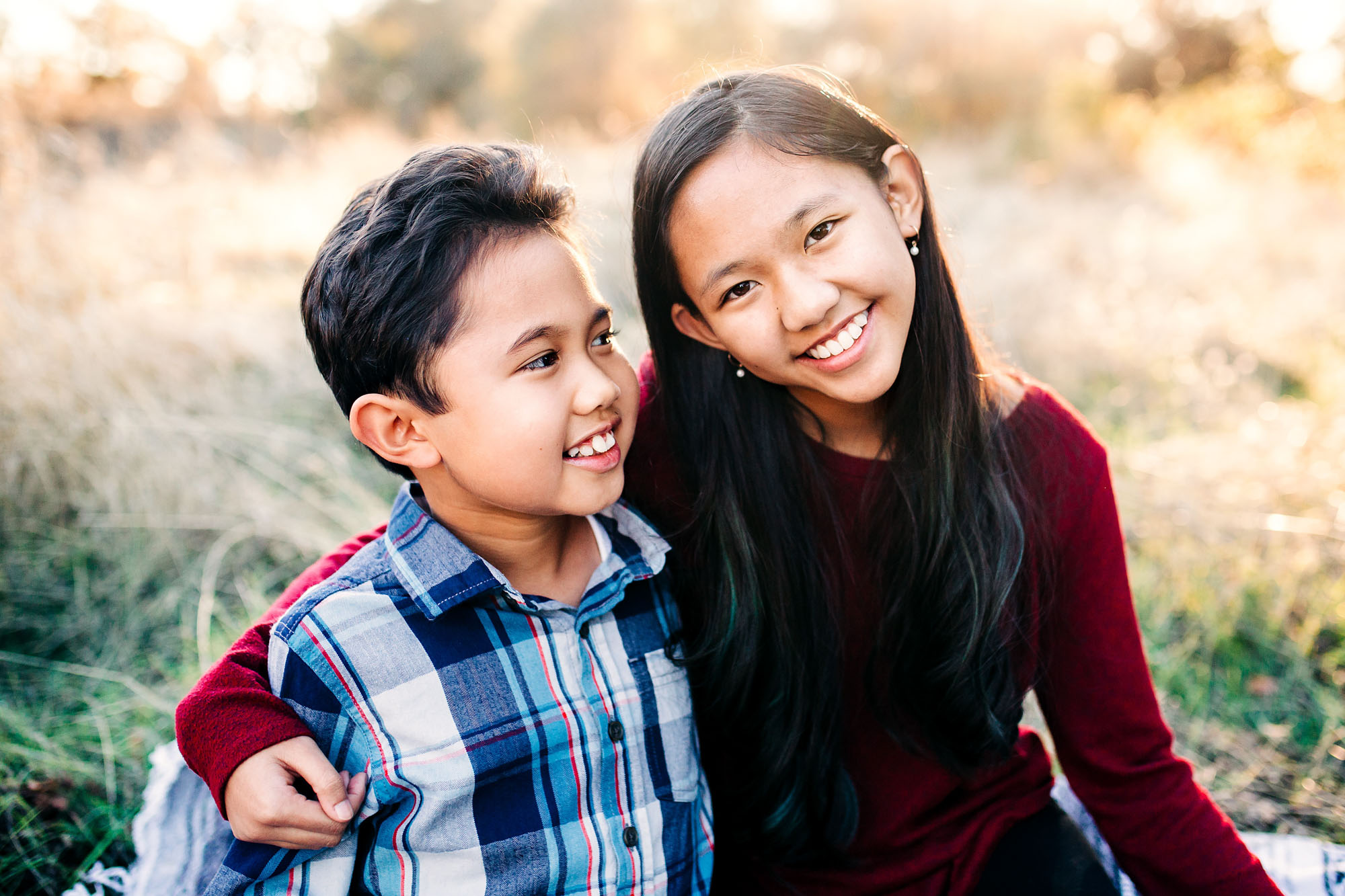 A sister and brother enjoy each other's company during a family lifestyle photo session with Amy Wright Photography.