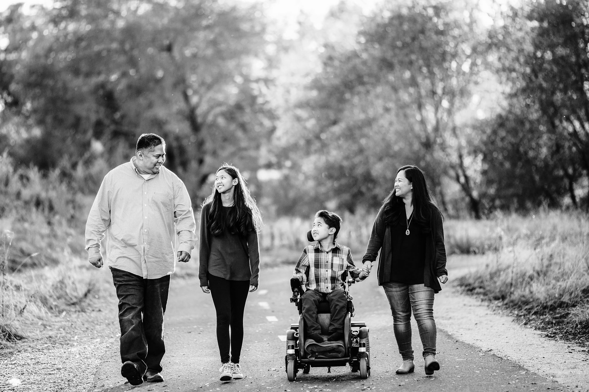 A family of four walks down a path together at the end of their family photo session with Amy Wright Photography, who is based out of Rocklin and Roseville, California.