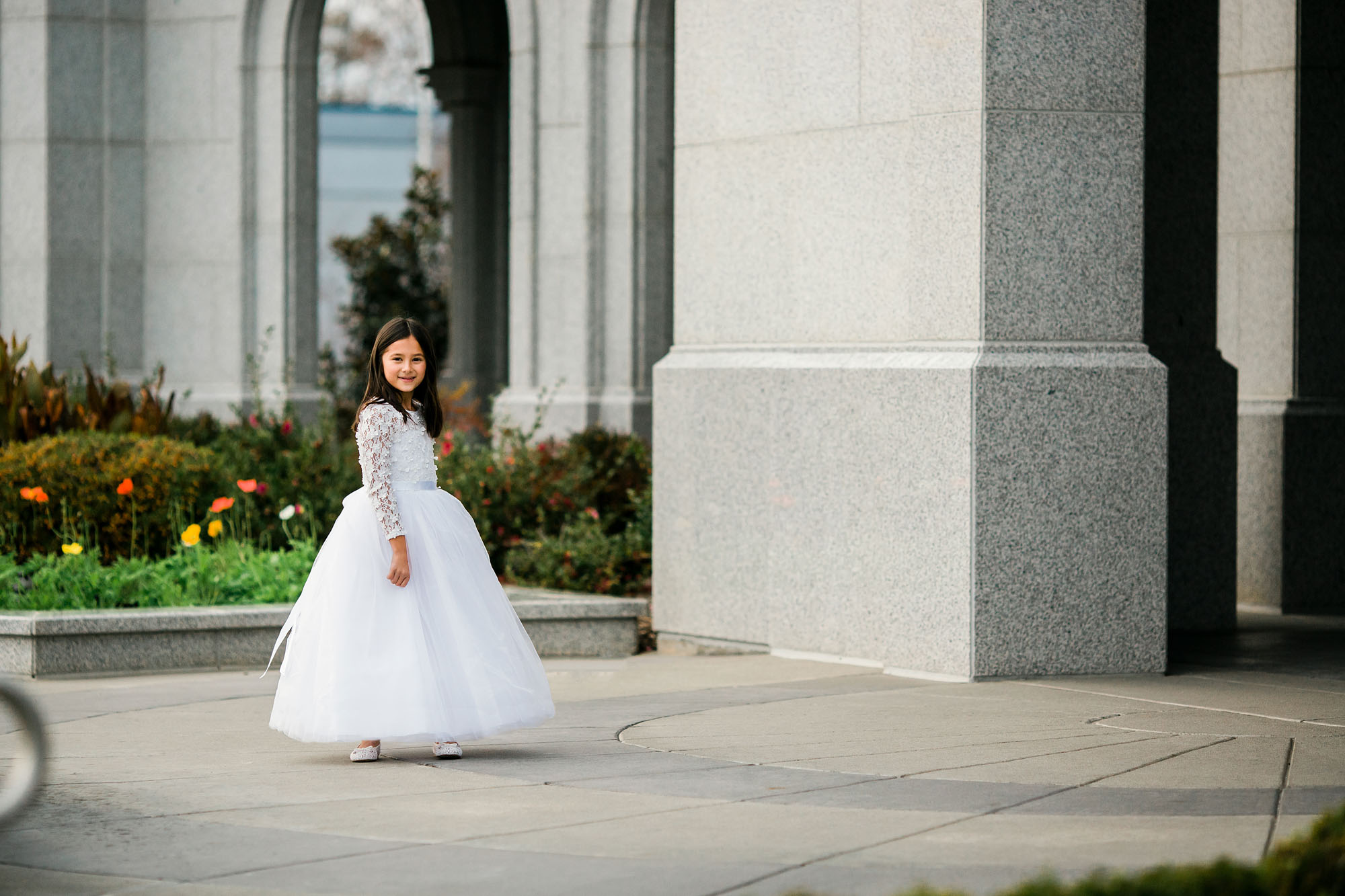 A girl in a white dress gets pictures taken at a temple in Folsom, California before she is baptized.
