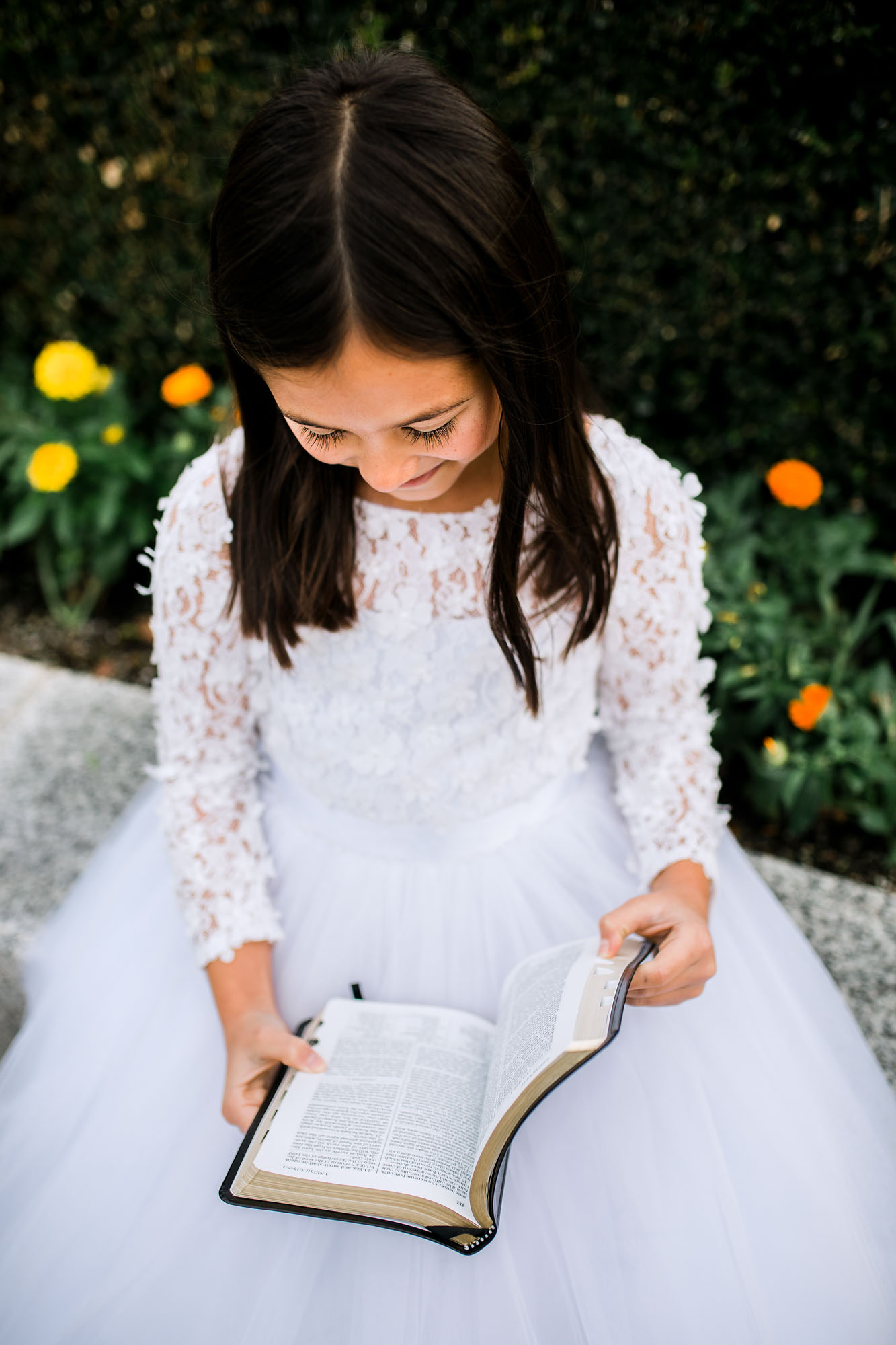 An 8-year-old girl in a white dress sits at the temple and reads her Book of Mormon during a photo session with Amy Wright Photography in Folsom, California.