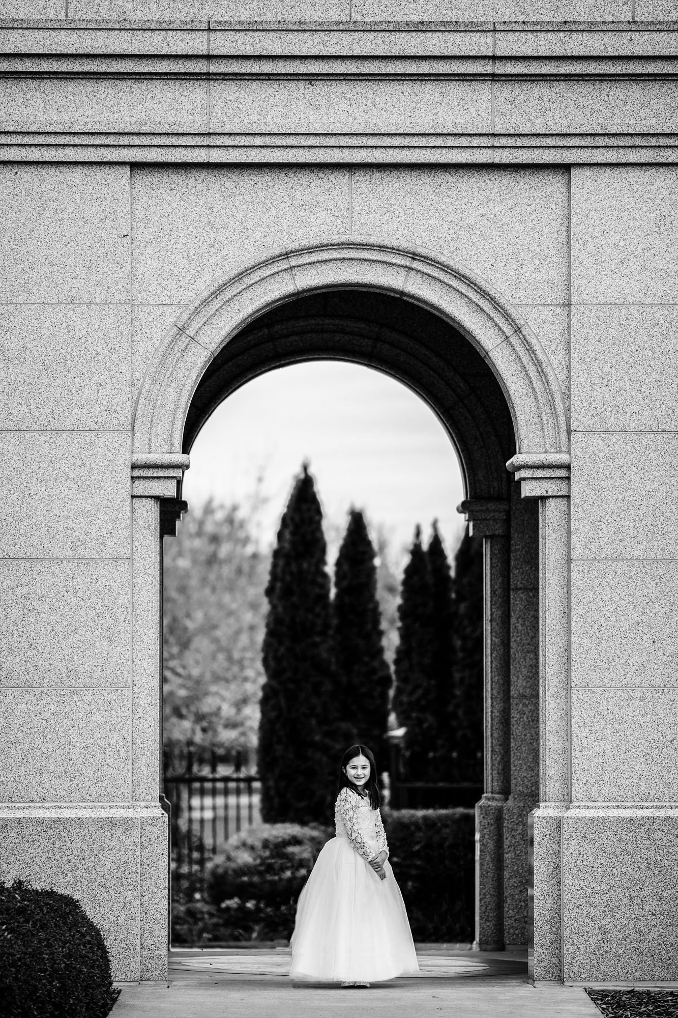 A girl stands under an arch of a temple of The Church of Jesus Christ of Latter-daySatins in Folsom, California during a photo session before she is baptized with Amy Wright Photography.