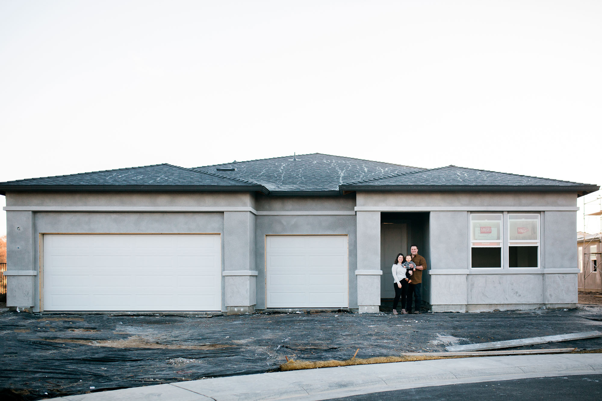 A family of three stands in front of the house they are building in the Sacramento area of Northern California.