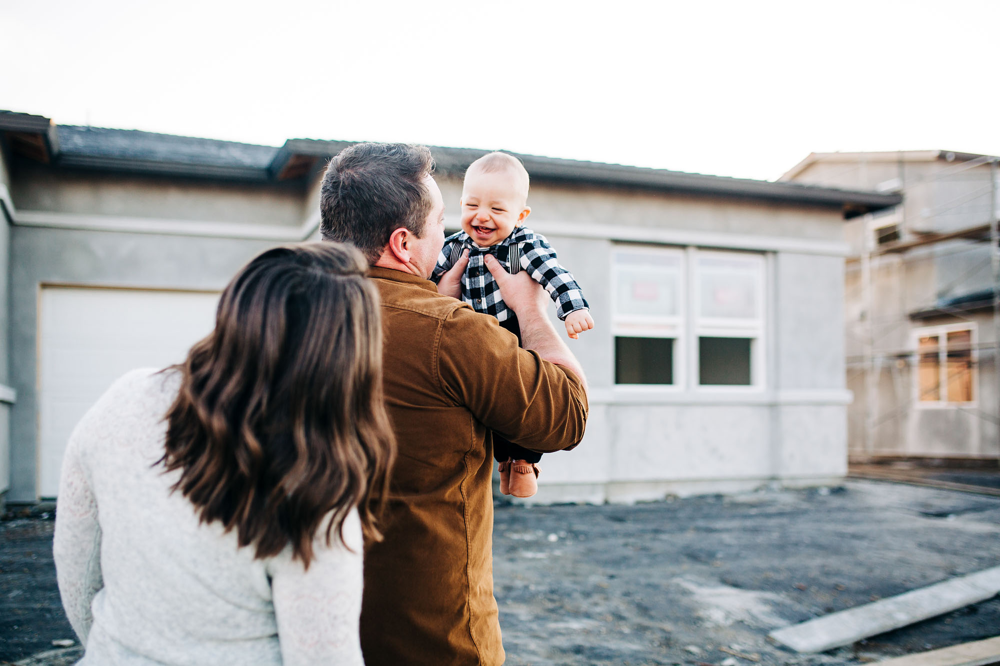 A father lifts up his happy baby boy as they stand in front of their new house during a lifestyle family photo session with Amy Wright Photography, based out of Roseville, California.