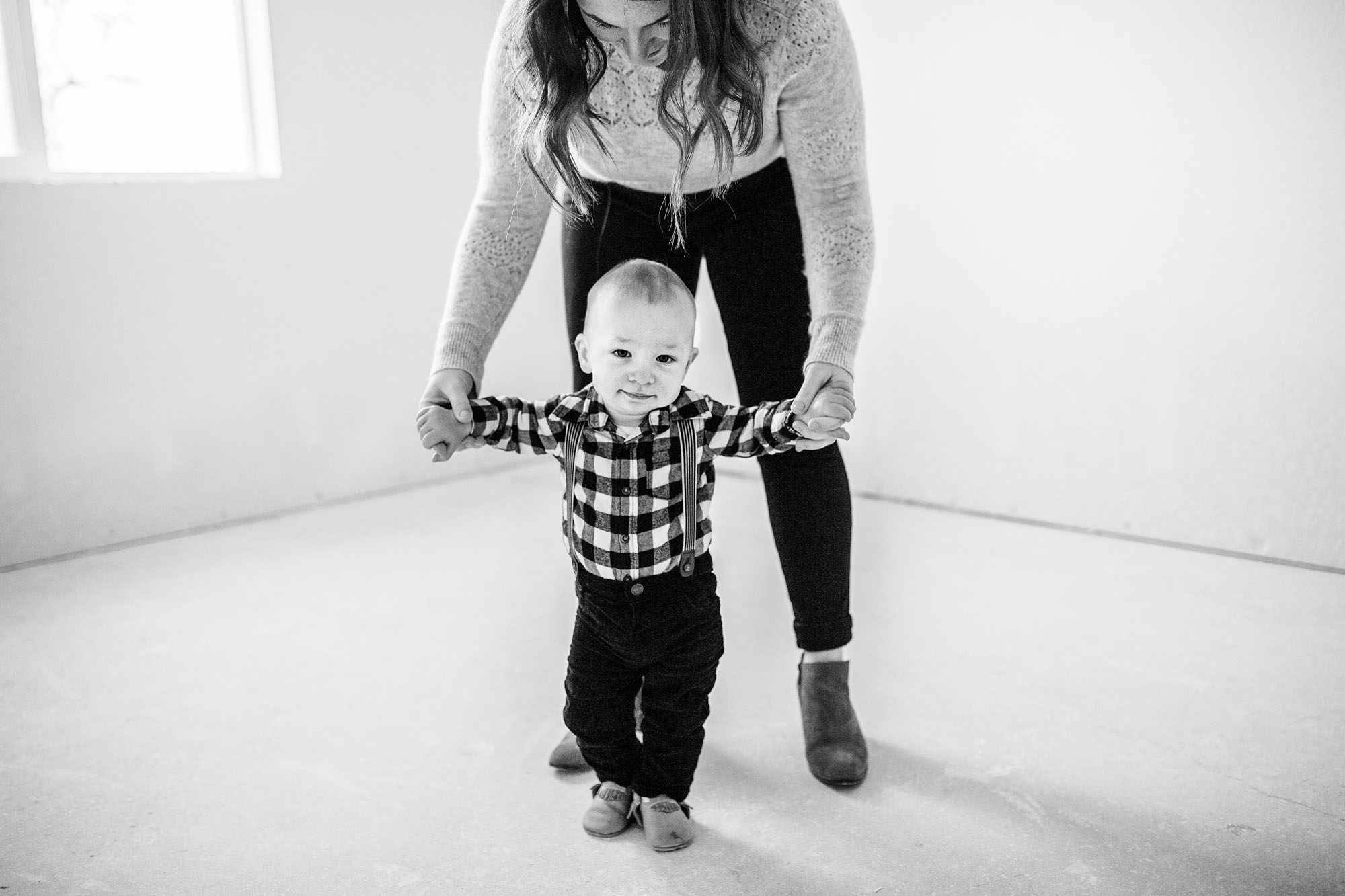 A baby holds onto his mama's hands while he tries to walk in his new home during a family photo session with Amy Wright Photography, based out of Sacramento, California.