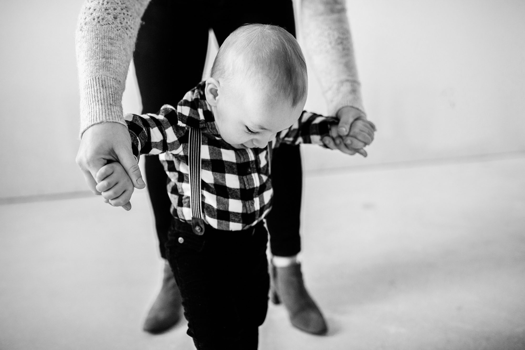 A toddler relies on his mother for help while he tried to walk in his home during a lifestyle photo session with Amy Wright Photography, based out of Roseville, California.