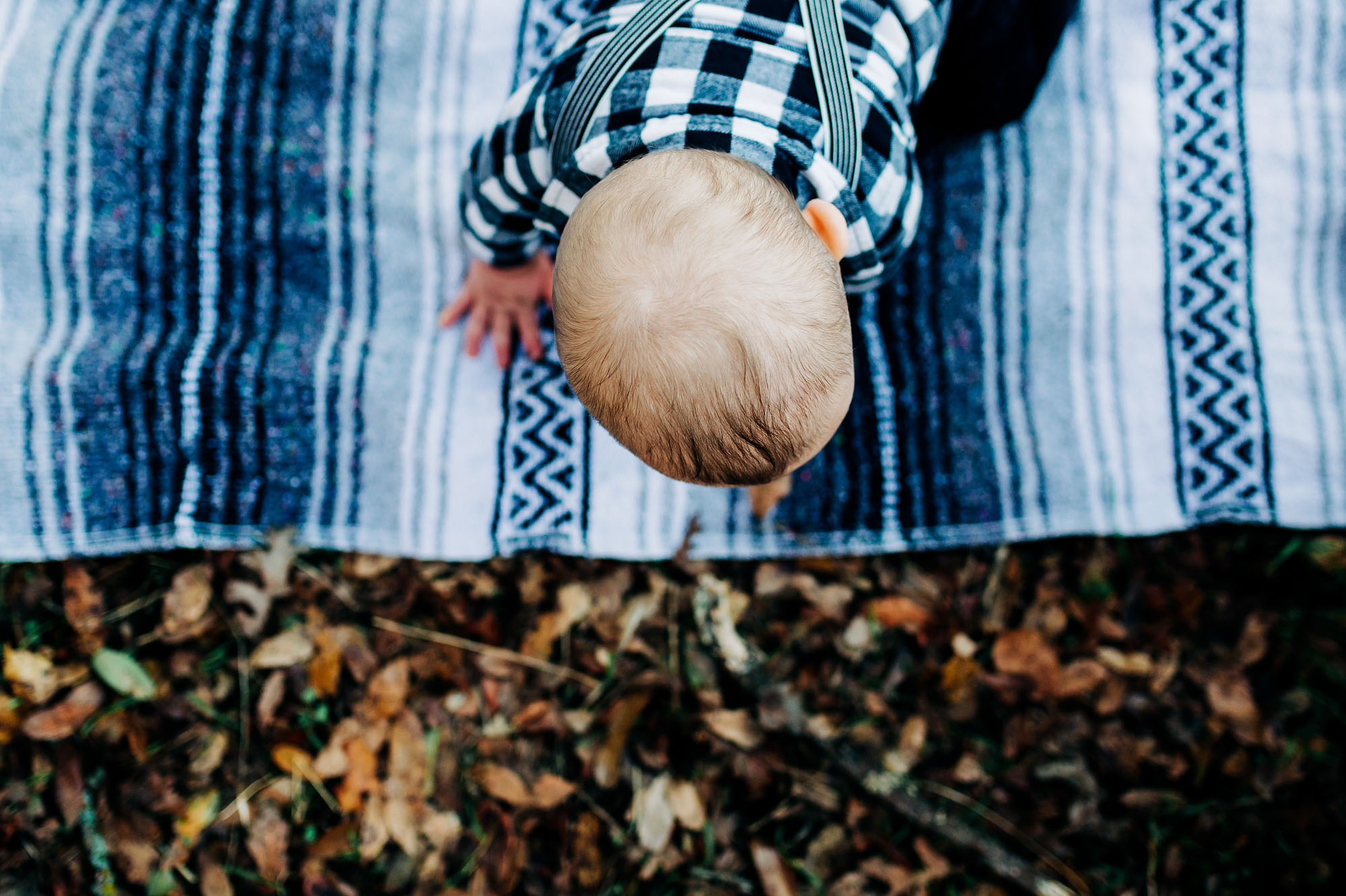 A baby crawls to the edge of a blanket during a family photo session in Roseville, California with Amy Wright Photography.
