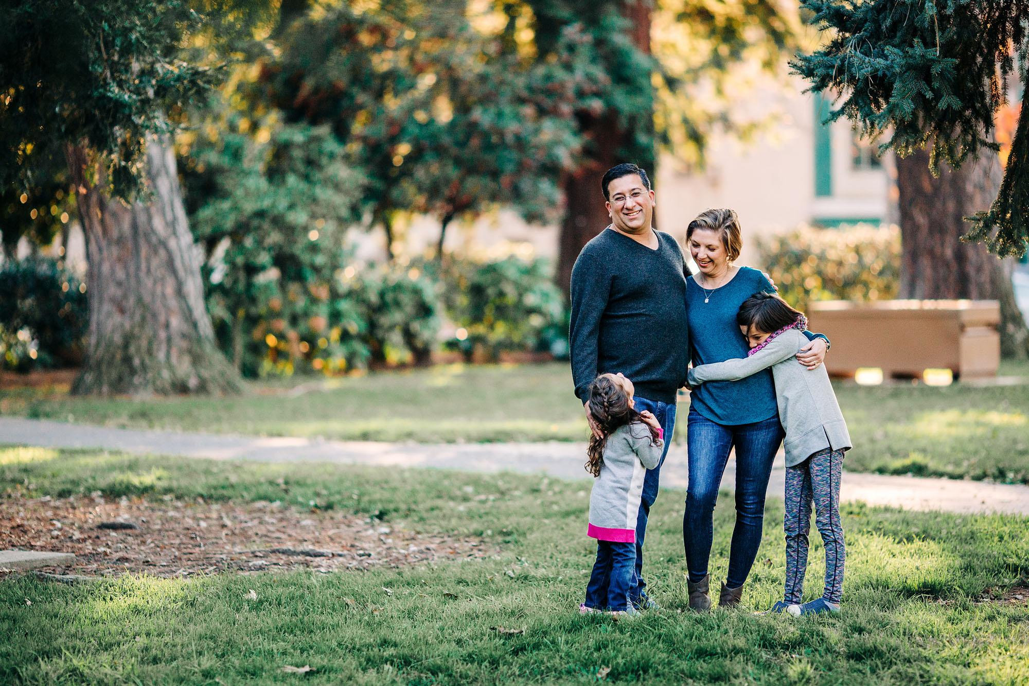 A family of four hugs during a photo shoot at Sacramento Capitol Park with photographer Amy Wright.