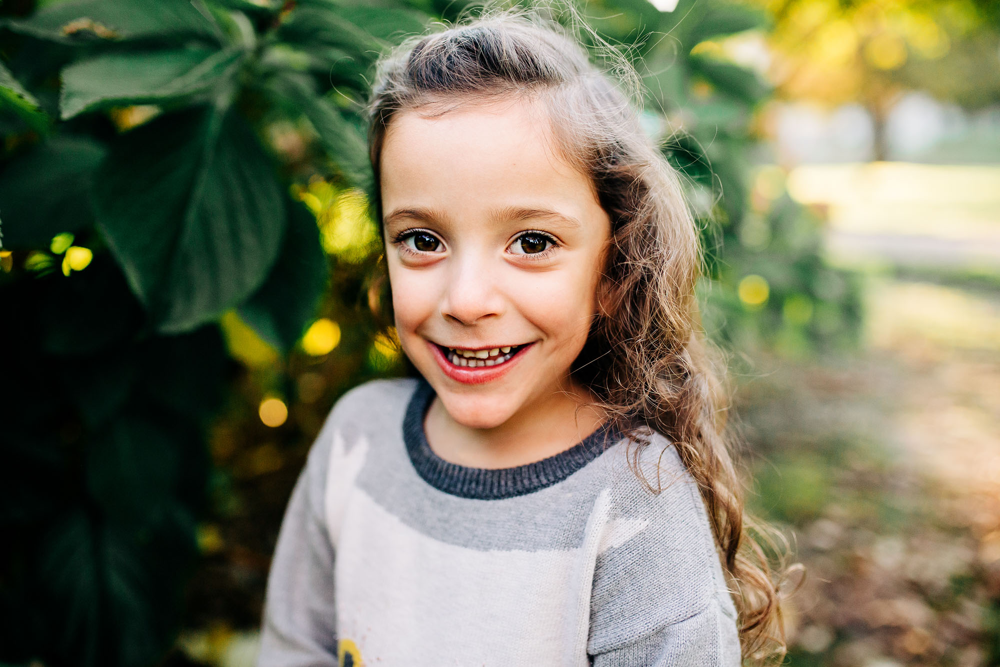 A portrait of a young girl smiling taken at Capitol Park in Sacramento, California by photographer Amy Wright.