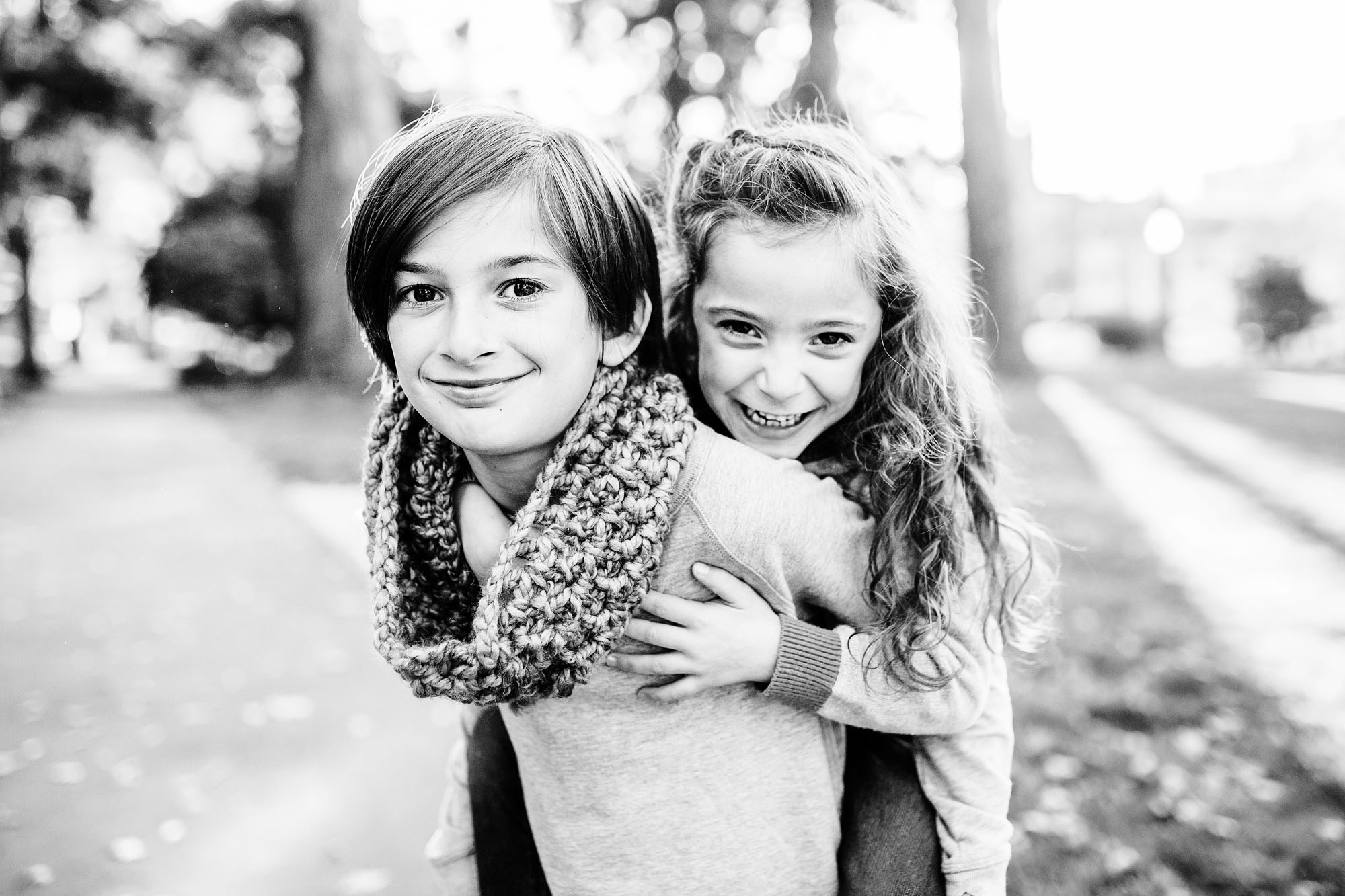 A black and white photograph of two sisters shows joy and love during a family photo session with Amy Wright, a photographer based out of Roseville, California.