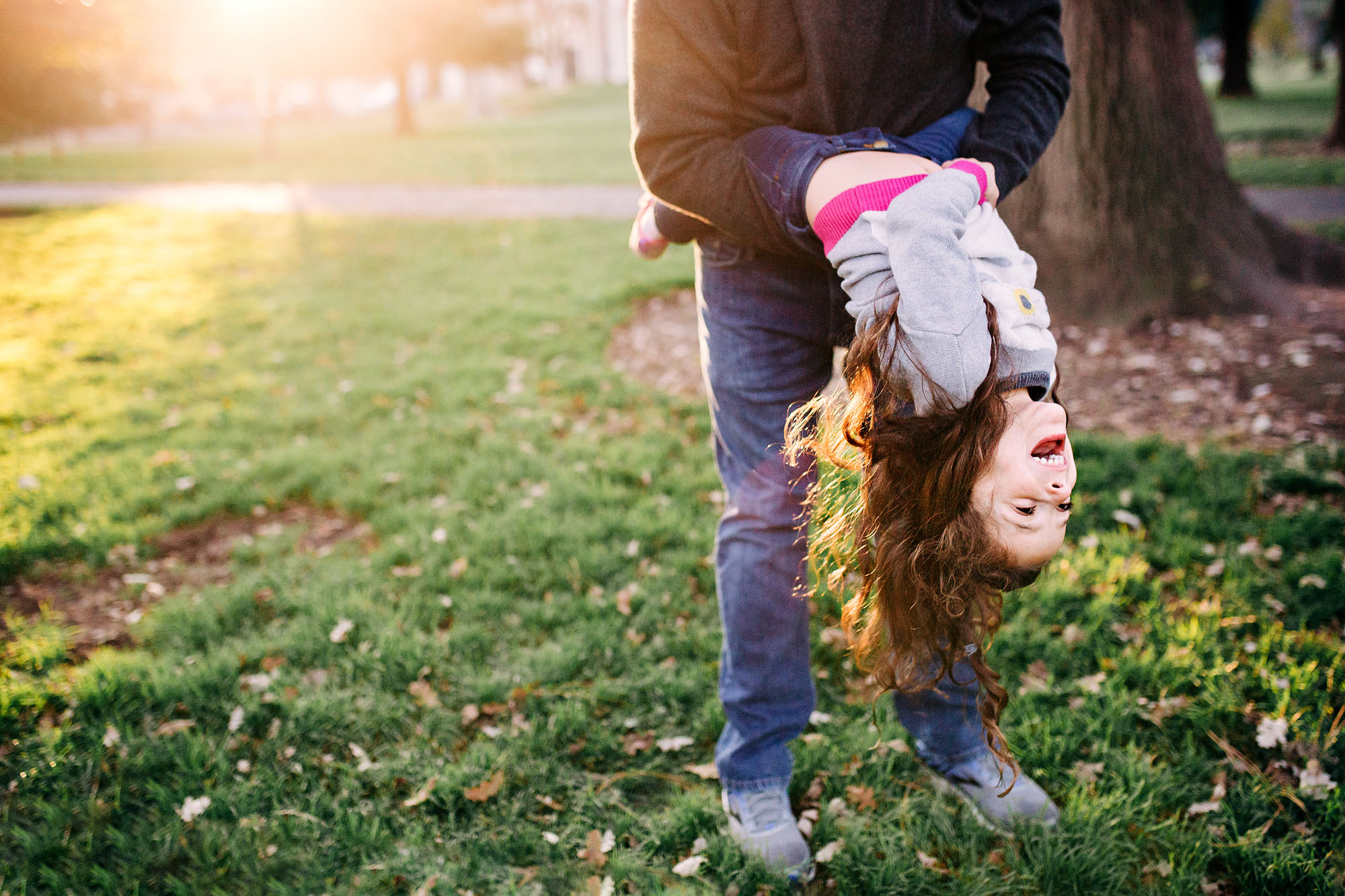 A father dips her daughter playfully during a fun family photo session with Amy Wright Photography in Roseville, California.