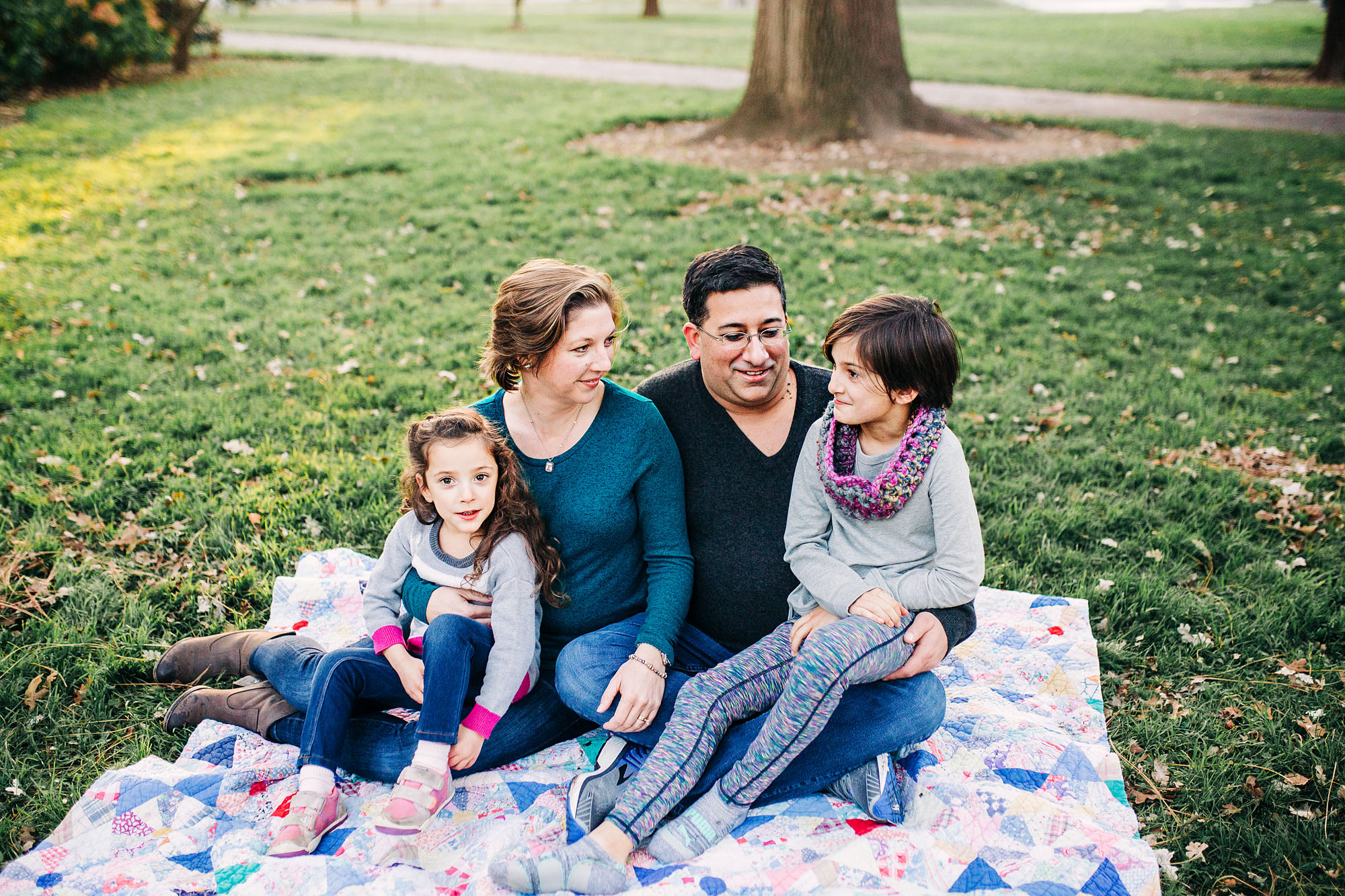 A family of four sits on a quilt at Capitol Park in Sacramento, California during a photo session with Amy Wright.