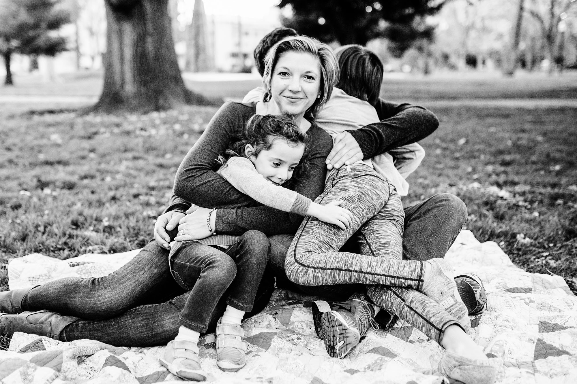 A black and white photo is taken of a family cuddling together during a photo session with Amy Wright Photography in Sacramento, California.