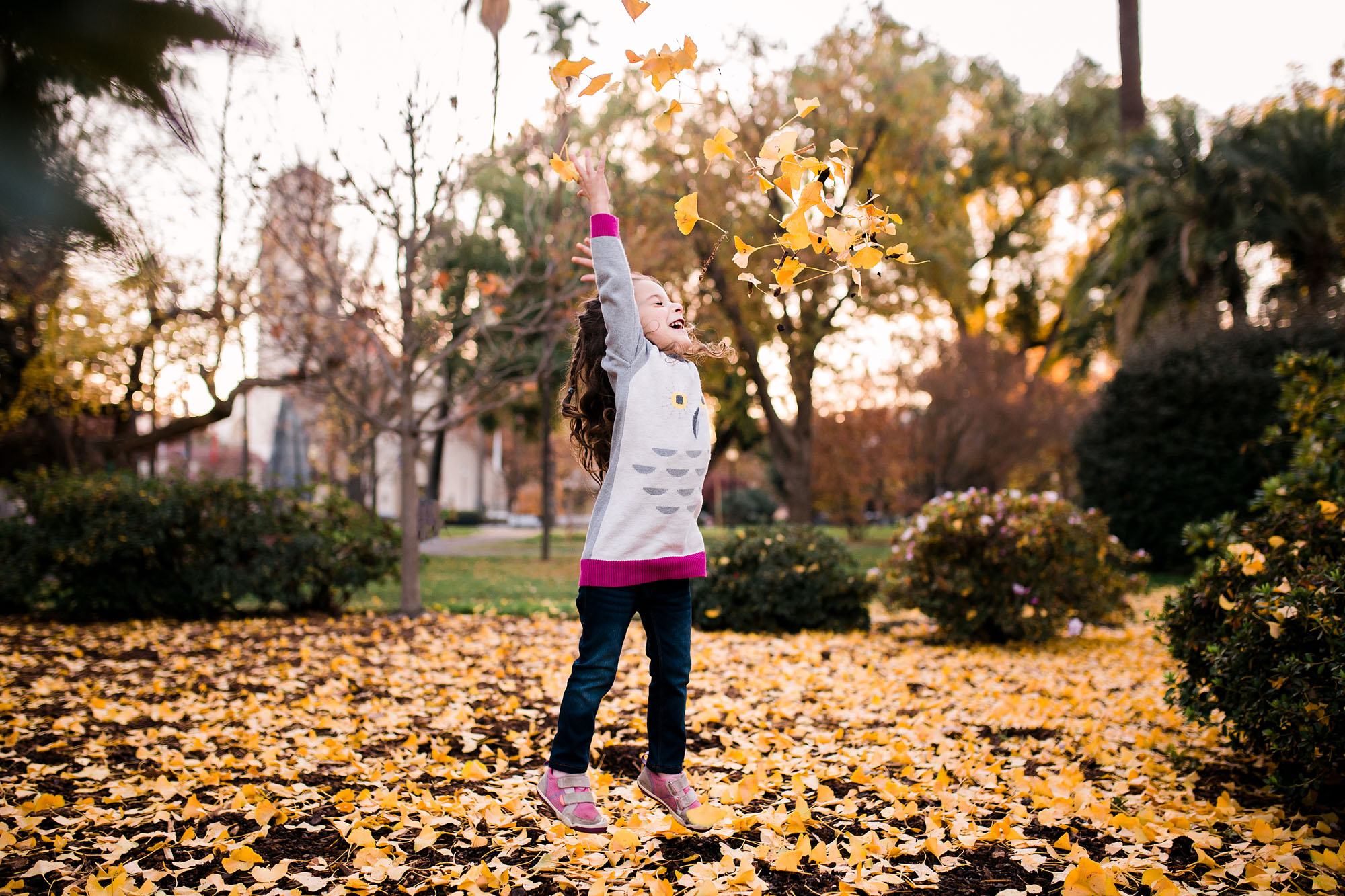 A girl joyfully throws leaves in the air during a lifestyle photo shoot with photographer Amy Wright, based out of Roseville, California.