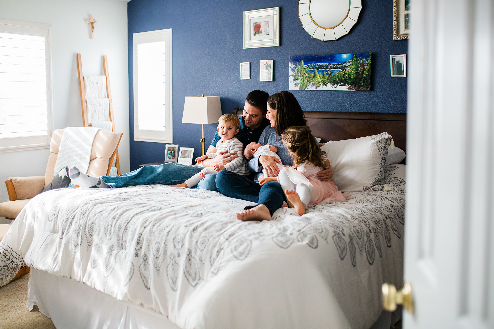 A new family of five sits on the bed admiring their newborn baby during a lifestyle photo session with Amy Wright, a photographer based out of Roseville, California.