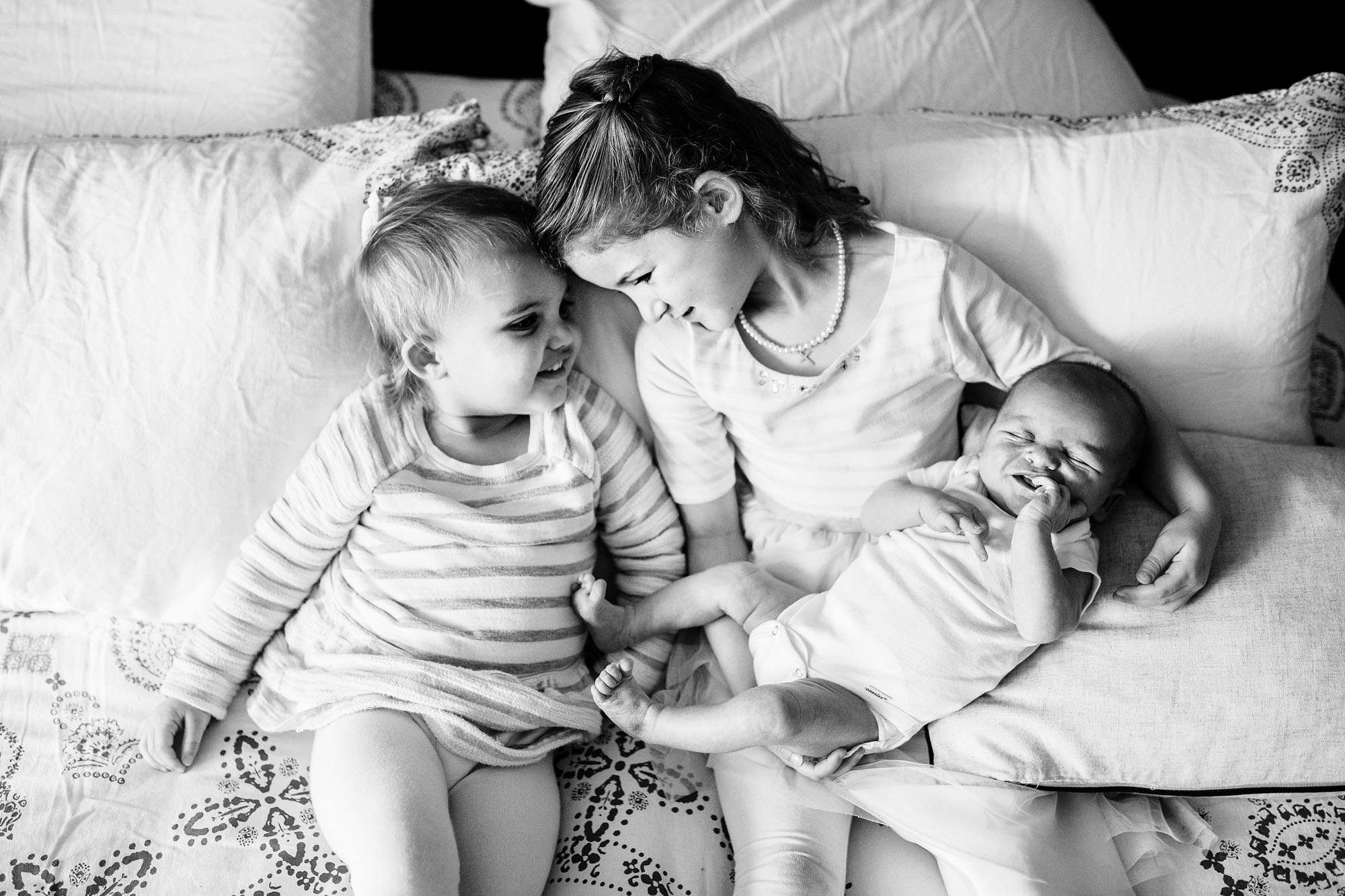 Siblings connect on a bed during a lifestyle newborn photo session with Amy Wright, a photographer based out of Sacramento, California.