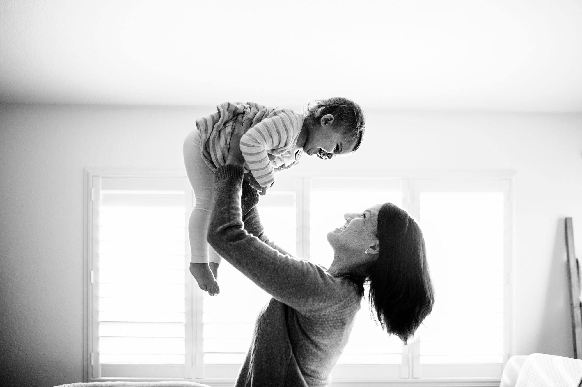 A mother lifts her daughter happily during an in-home lifestyle photo session in Roseville, Califonria with Amy Wright Photography.