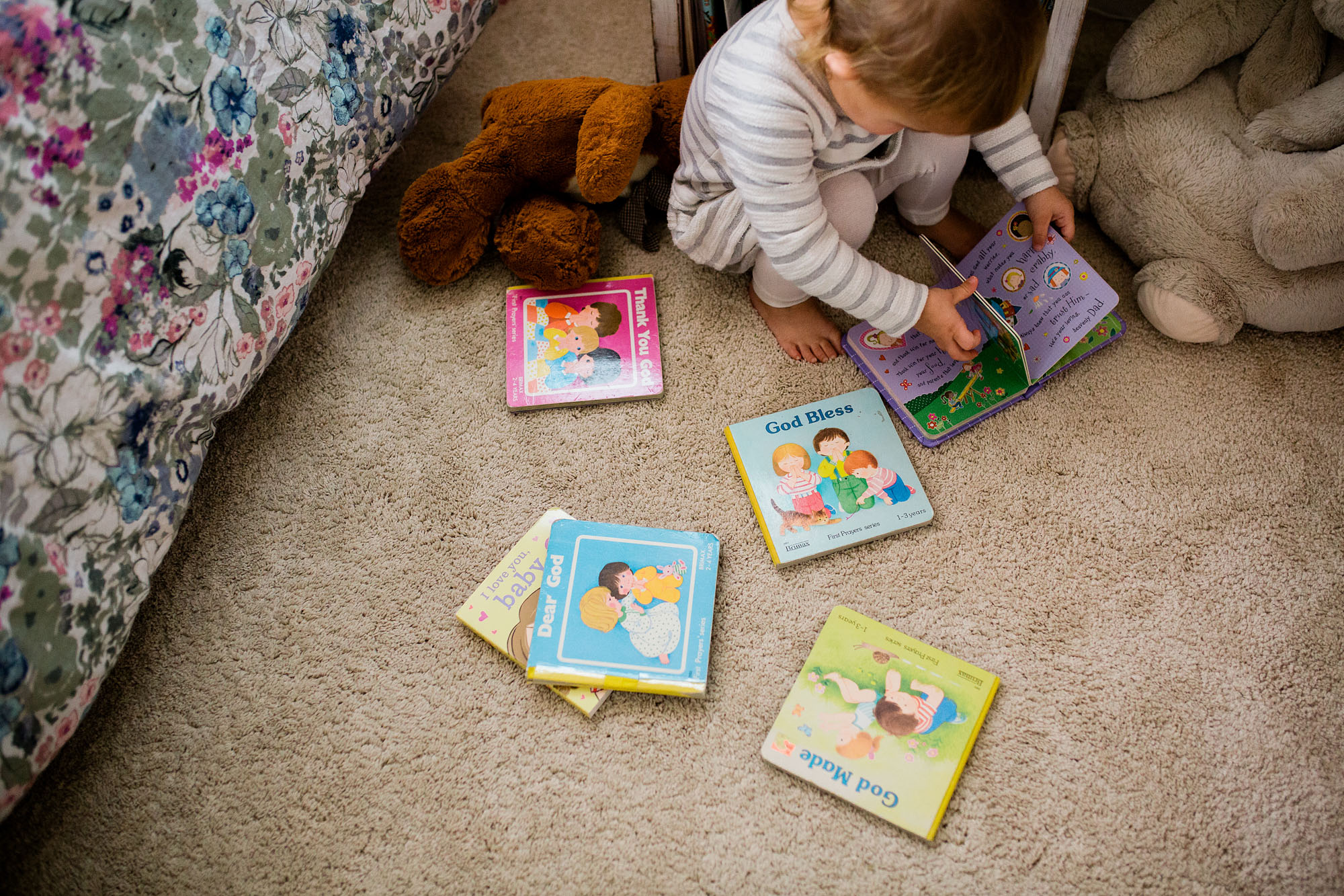 A toddler reads books in her room during a lifestyle newborn session wtih Amy Wright, a photographer based out of Sacramento, California.