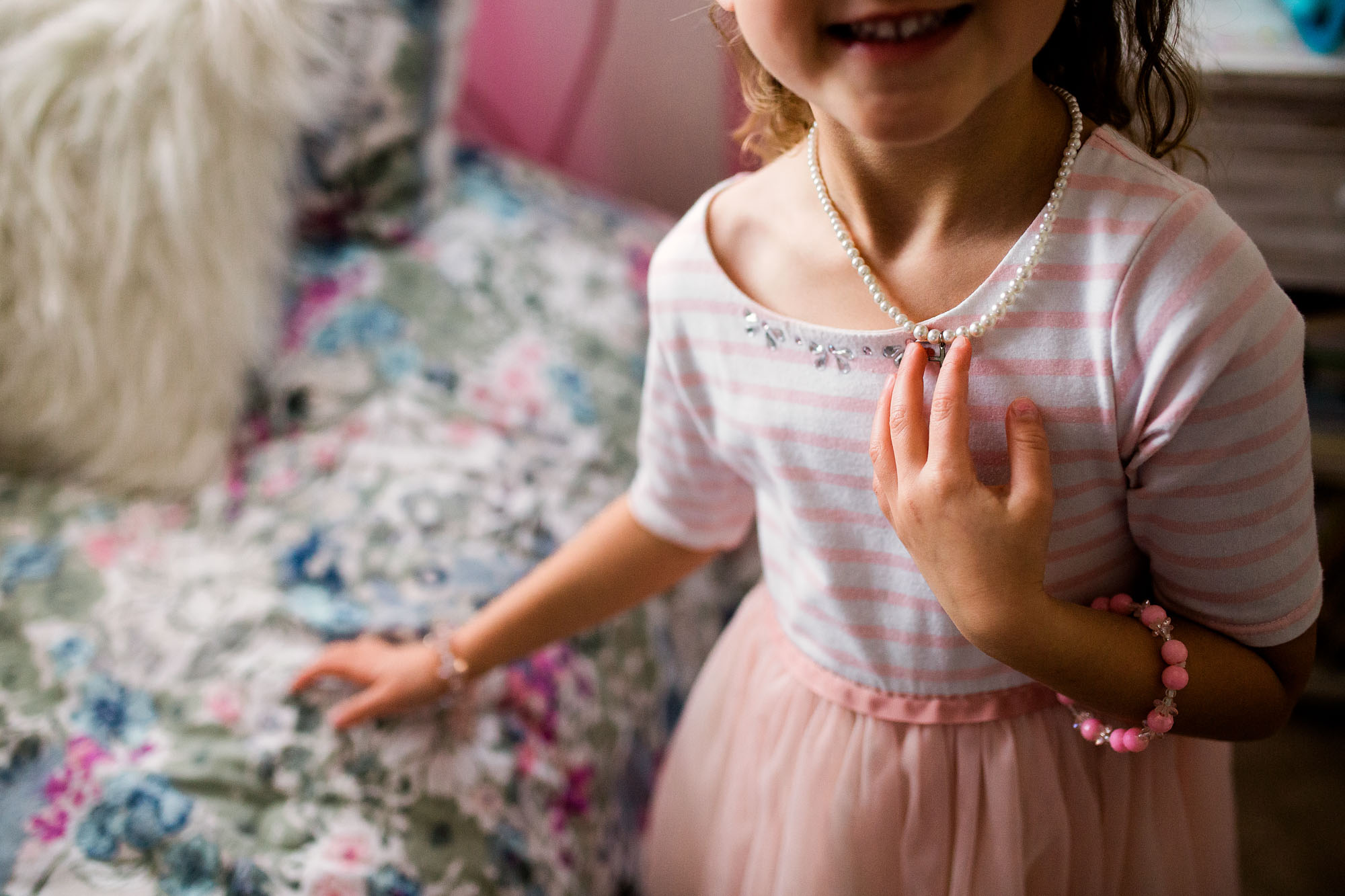 A young girl touches her necklace and smiles during an in-home lifestyle photo session in Roseville, California.