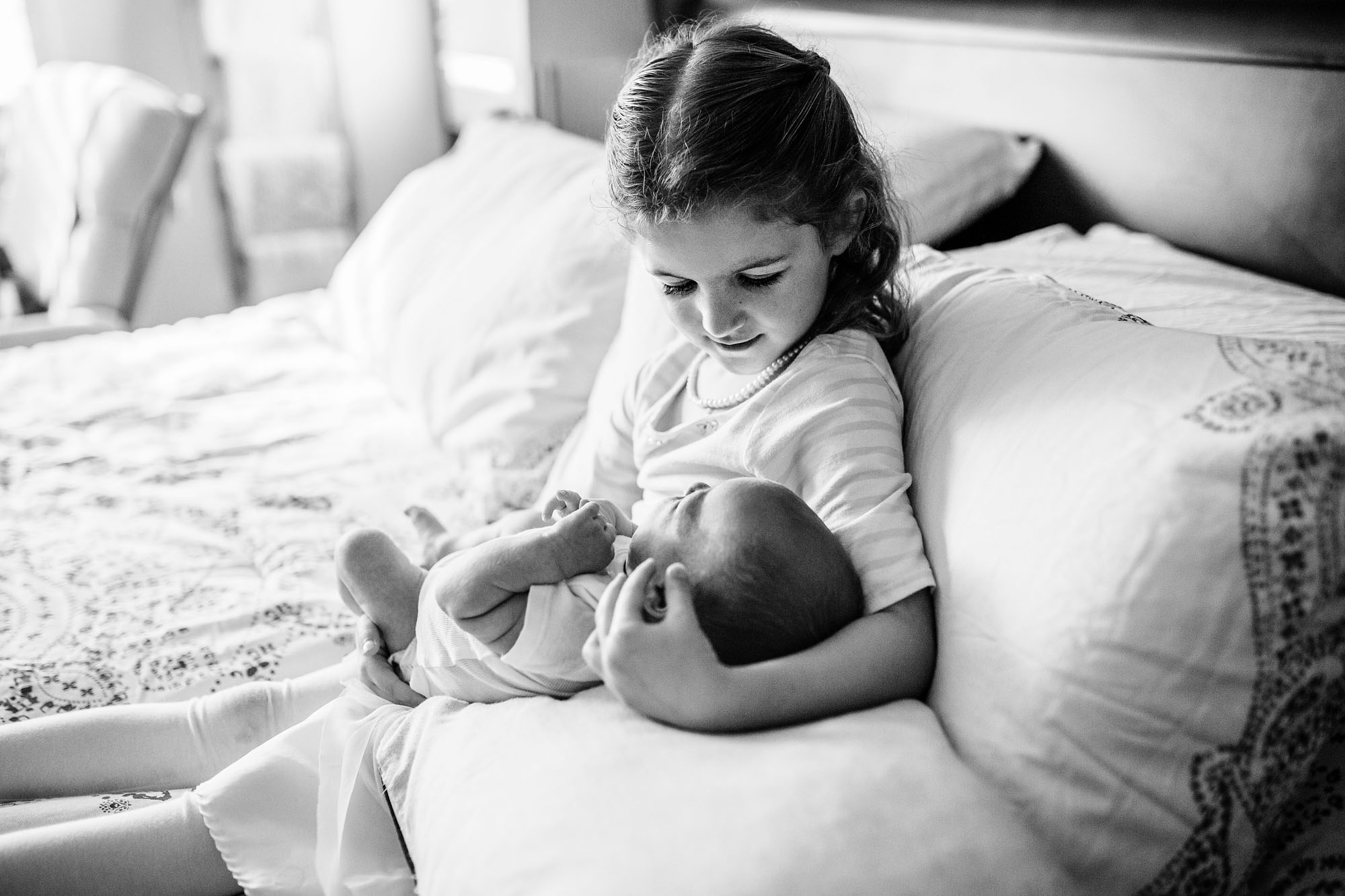 A big sister carefully holds her baby brother at home during a newborn photo session in Sacramento, California.