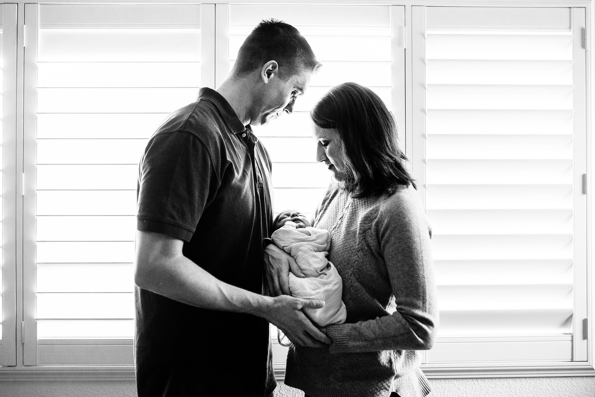 A mother and father admire their newborn baby as their pictures are taken by Amy Wright, a lifestyle photographer based out of Roseville, California.