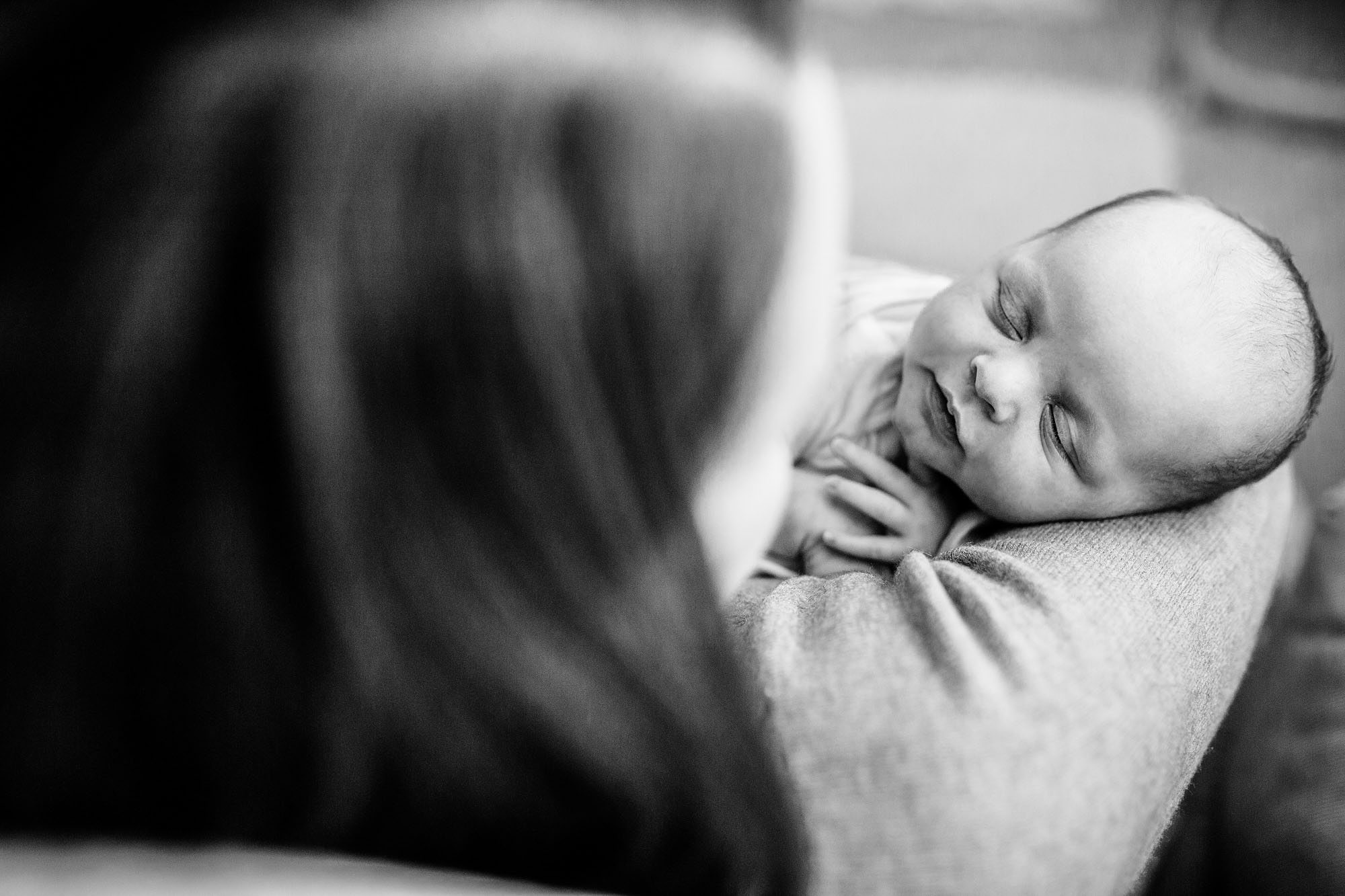 A newborn sleeps and is held by his mother during a peaceful in-home lifestyle photo session in Sacramento, California.