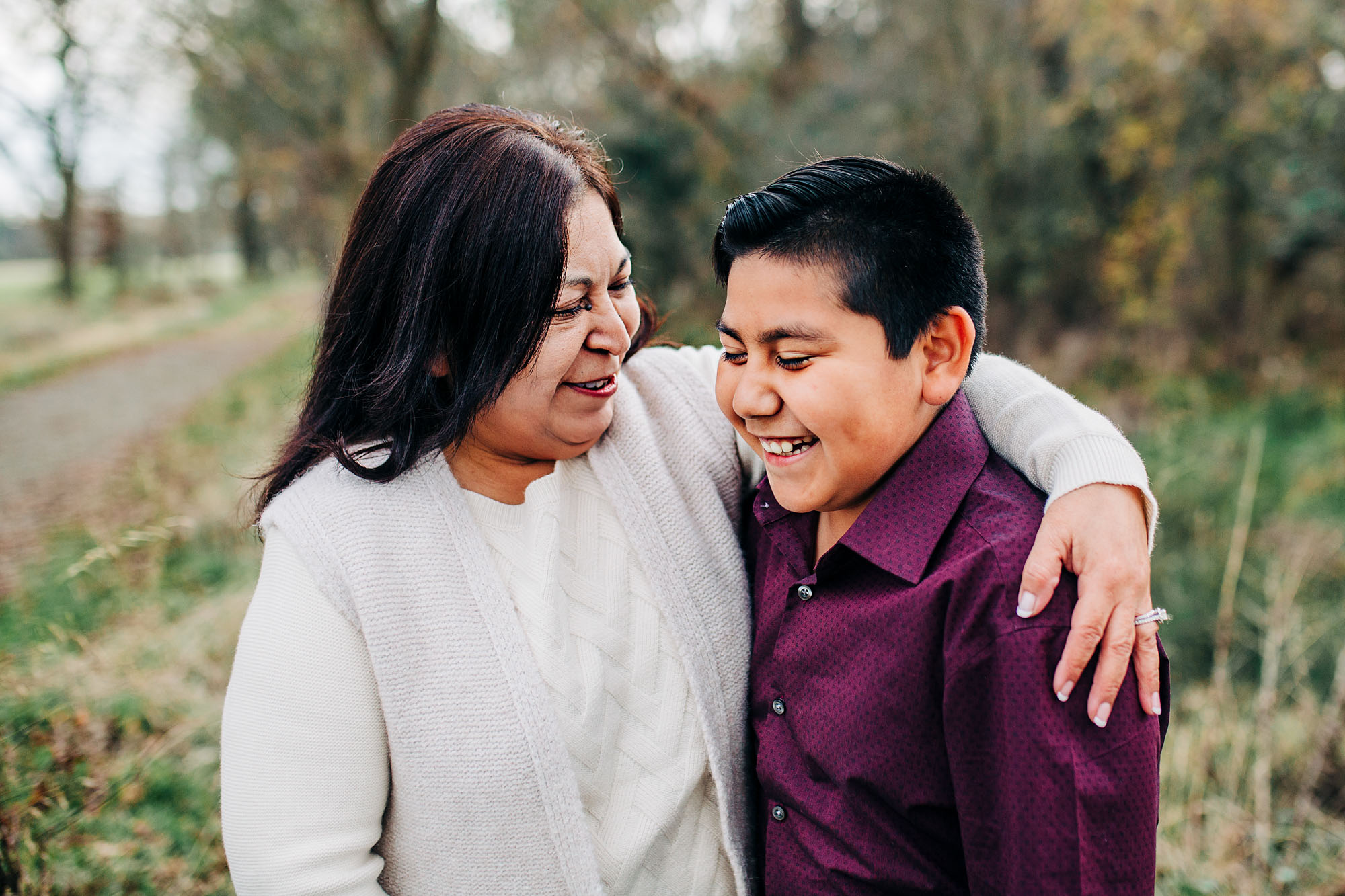 A grandmother and grandson laugh and put their arms around each other during an extended family photo session with Amy Wright Photo, based out of Roseville, California.