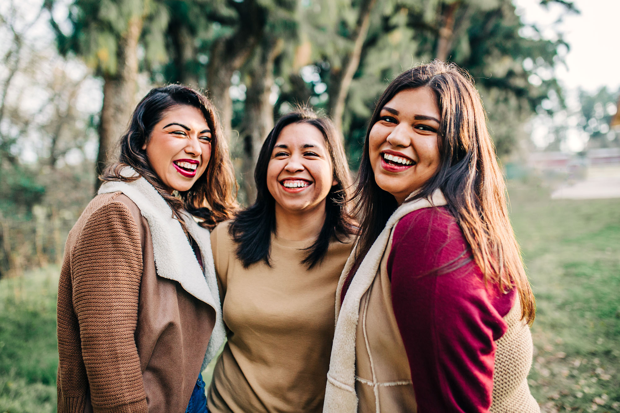 Three sisters put their arms around each other and have fun during a photo session with Amy Wright Photo, a photographer in Roseville, California.