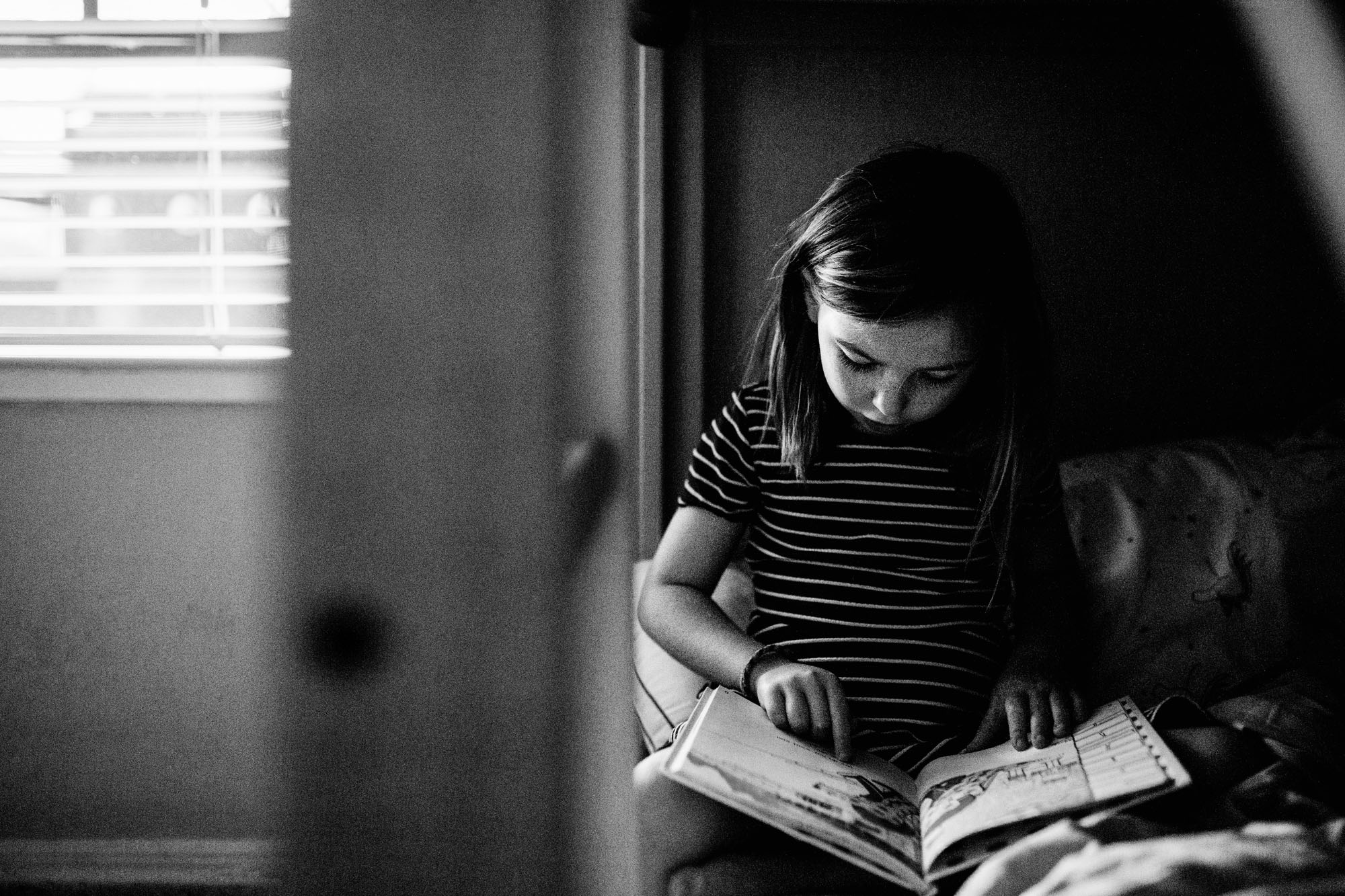A girl sits on her bed and reads during an in-home lifestyle family photo session with Amy Wright Photo in Roseville, California.