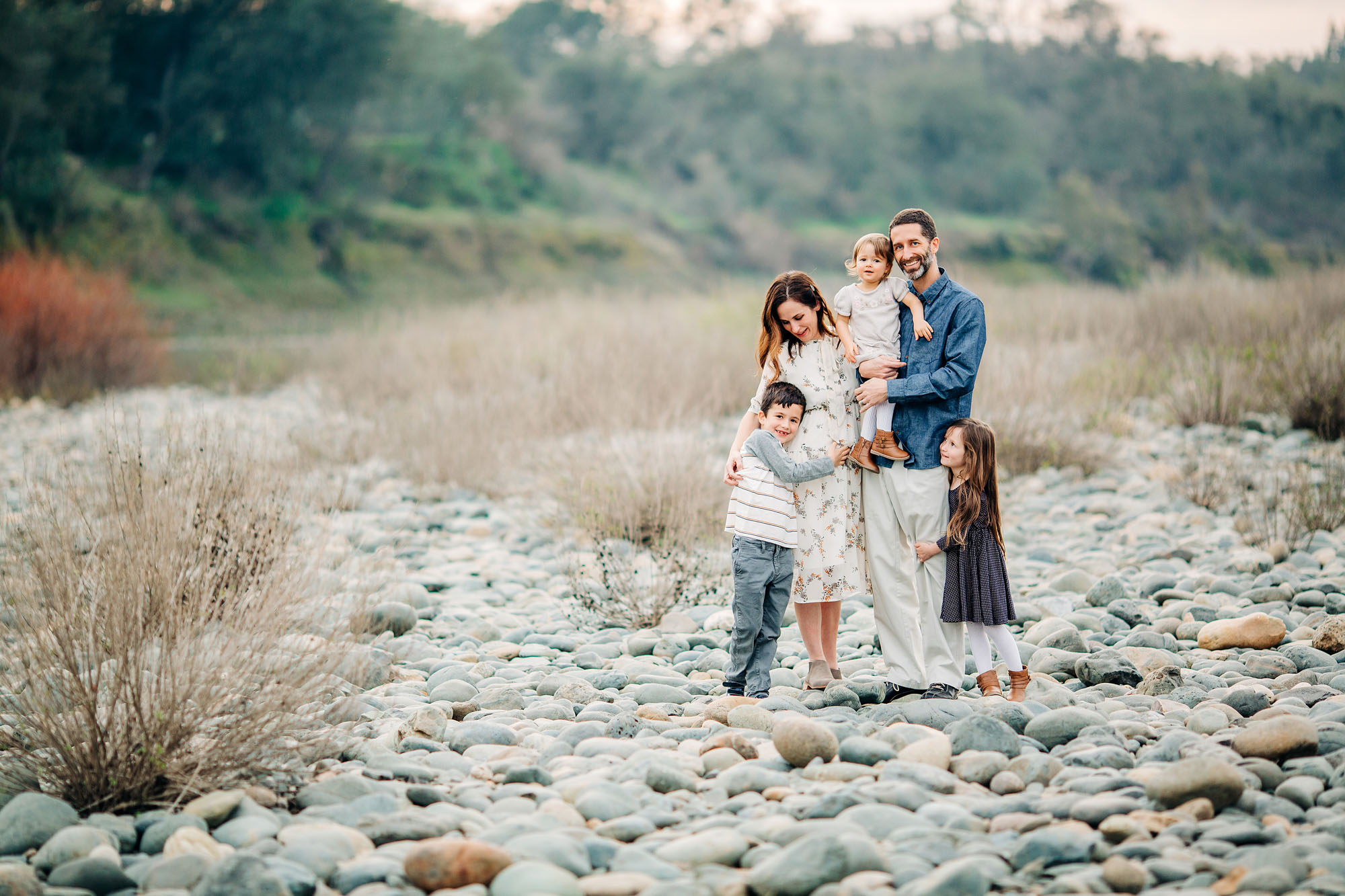 A family of five stands by a river near the Sacramento area during a photo session with Amy Wright, a photographer based out of Roseville, California.