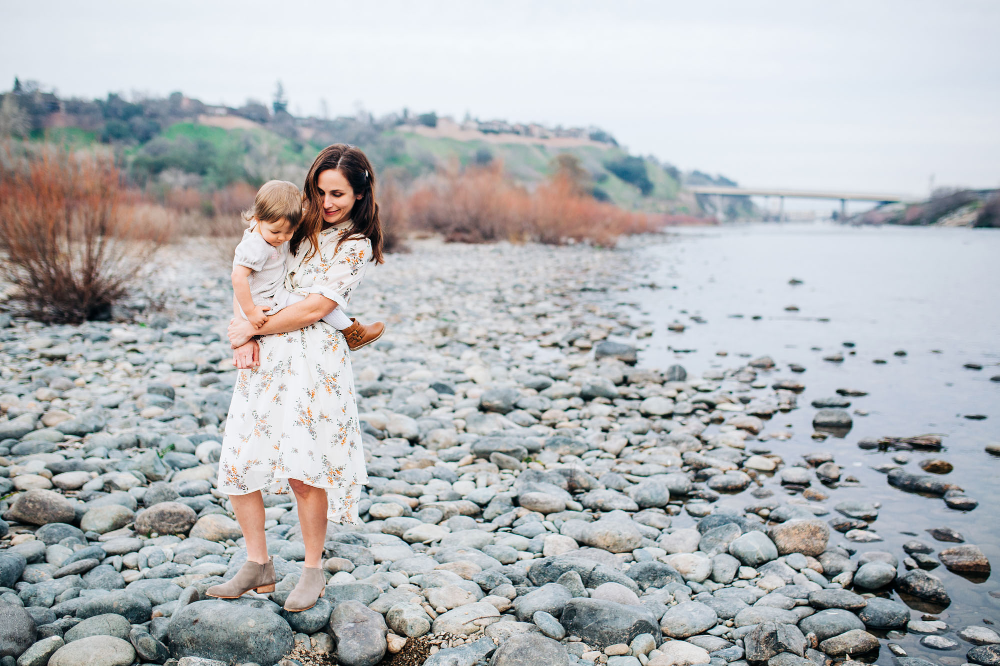 A mother and daughter walk on rocks by some water in the Sacramento area during a family photo session with photographer Amy Wright.