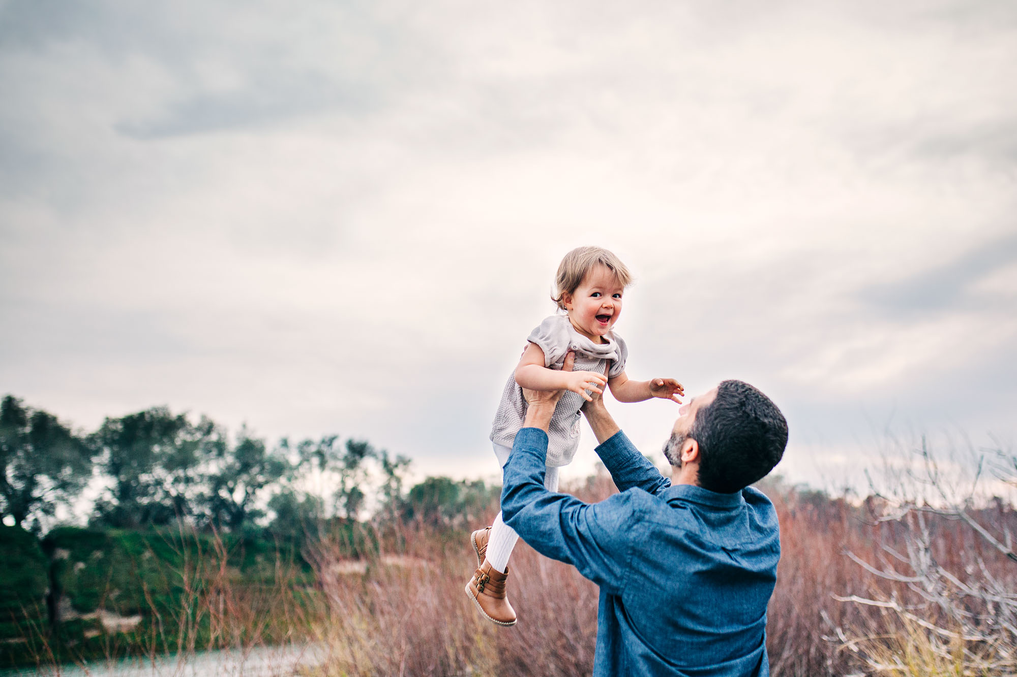 A little girl has fun as her father tosses her in the air during a lifestyle family photo session with Amy Wright, a photographer based in Roseville, California.