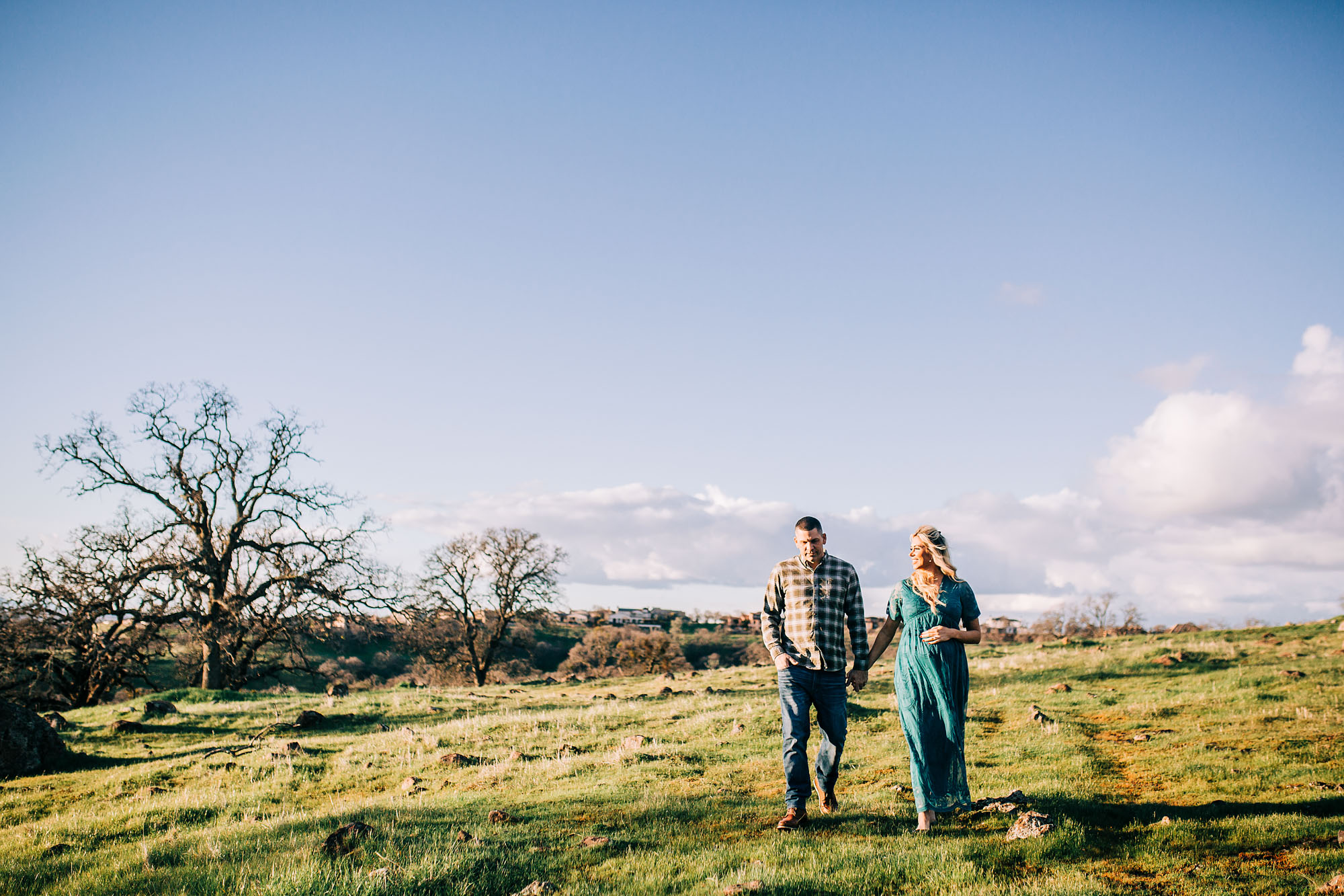 A couple walks together during a maternity photo session in the Roseville area of California with Amy Wright Photography.