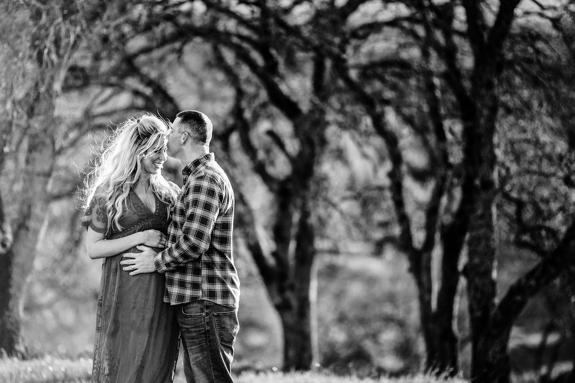 A husband kisses his wife during a lifestyle maternity session in Rocklin, California with Amy Wrigh tas the photographer.