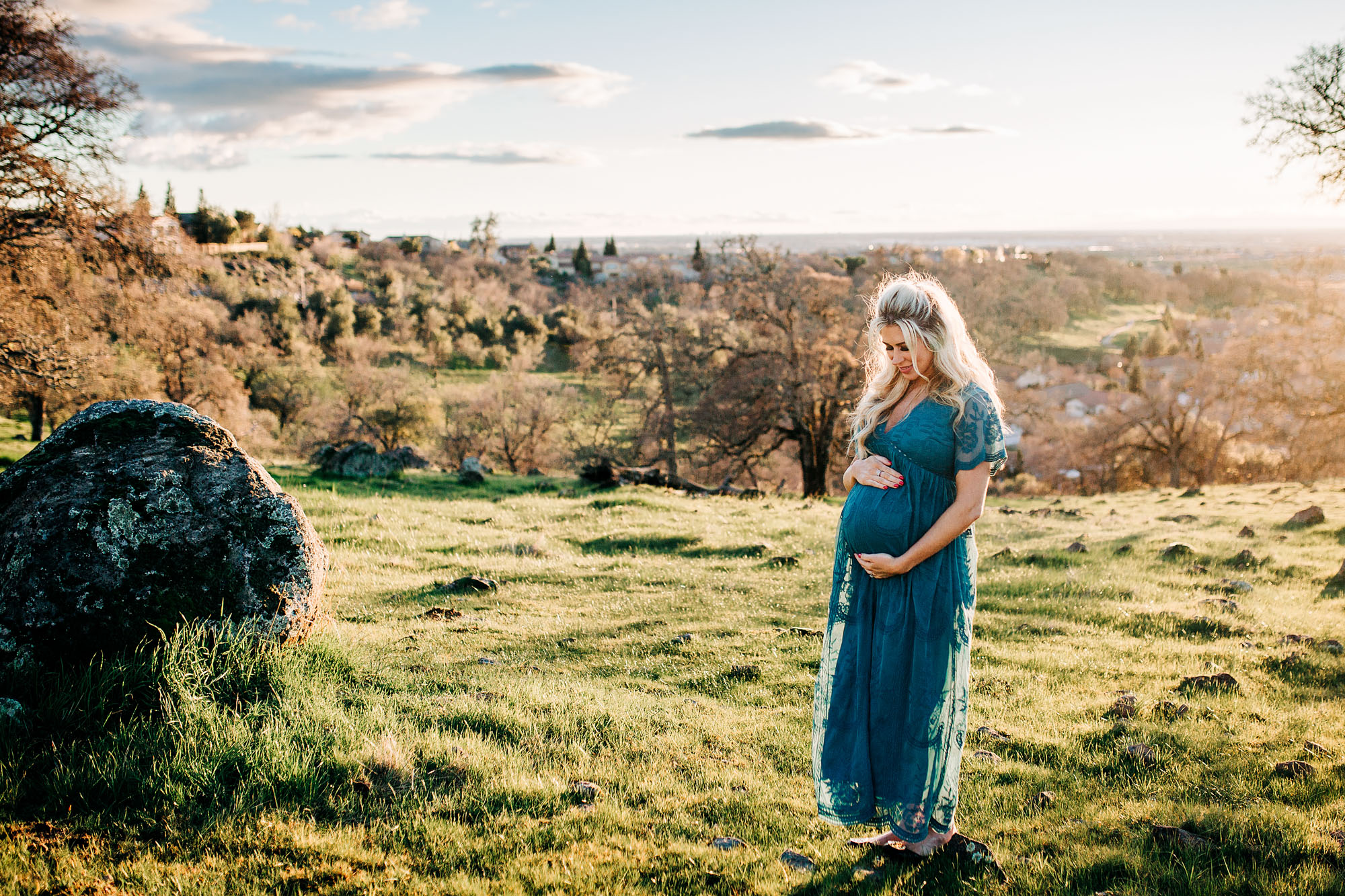 A beautiful mother-to-be looks at her belly during a lifestyle maternity session with Amy Wright, a photographer based out of Roseville, California.