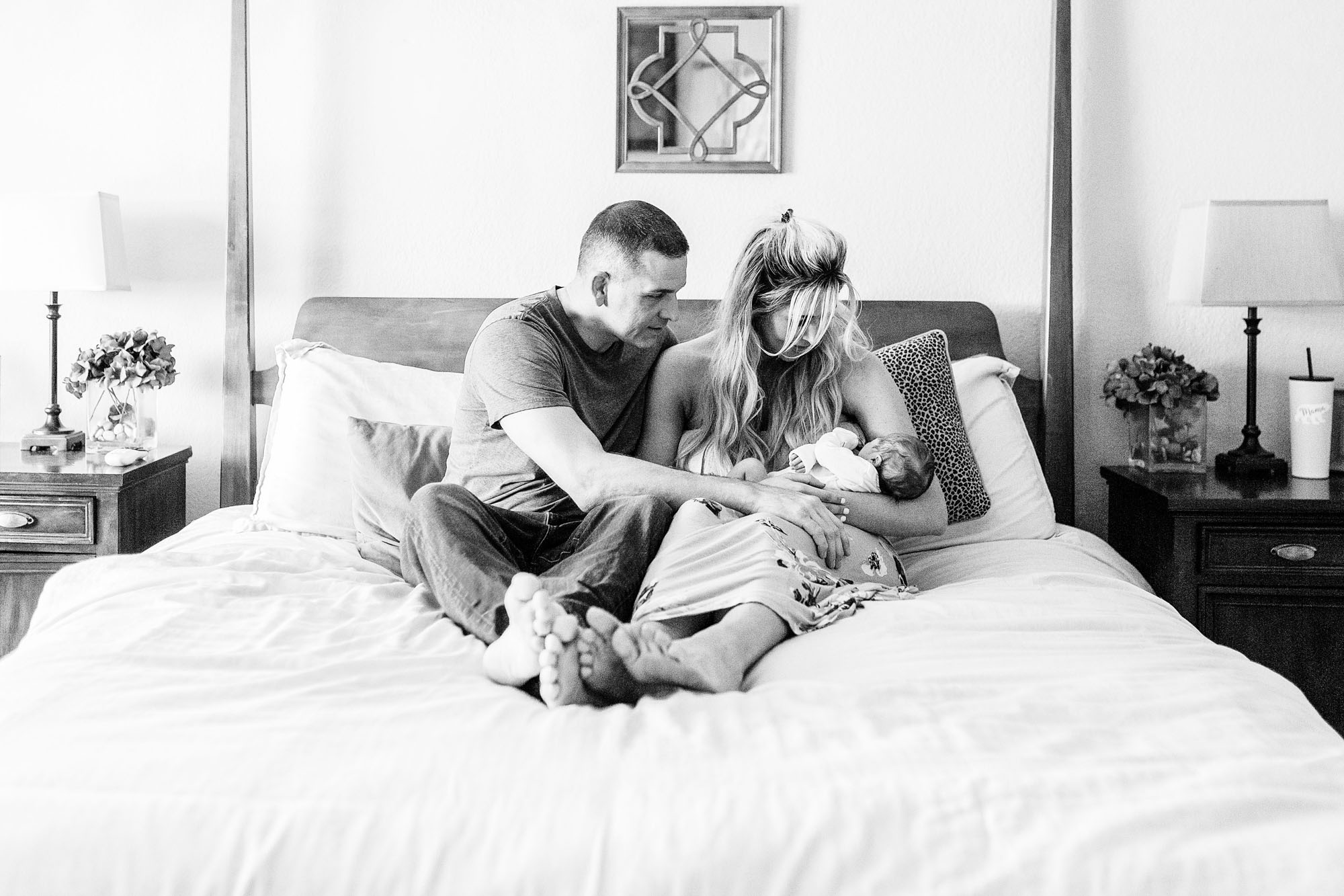 A family sits on a bed while the parents admire their newborn during a lifestyle newborn photo session with photographer Amy Wright in Rocklin, California.