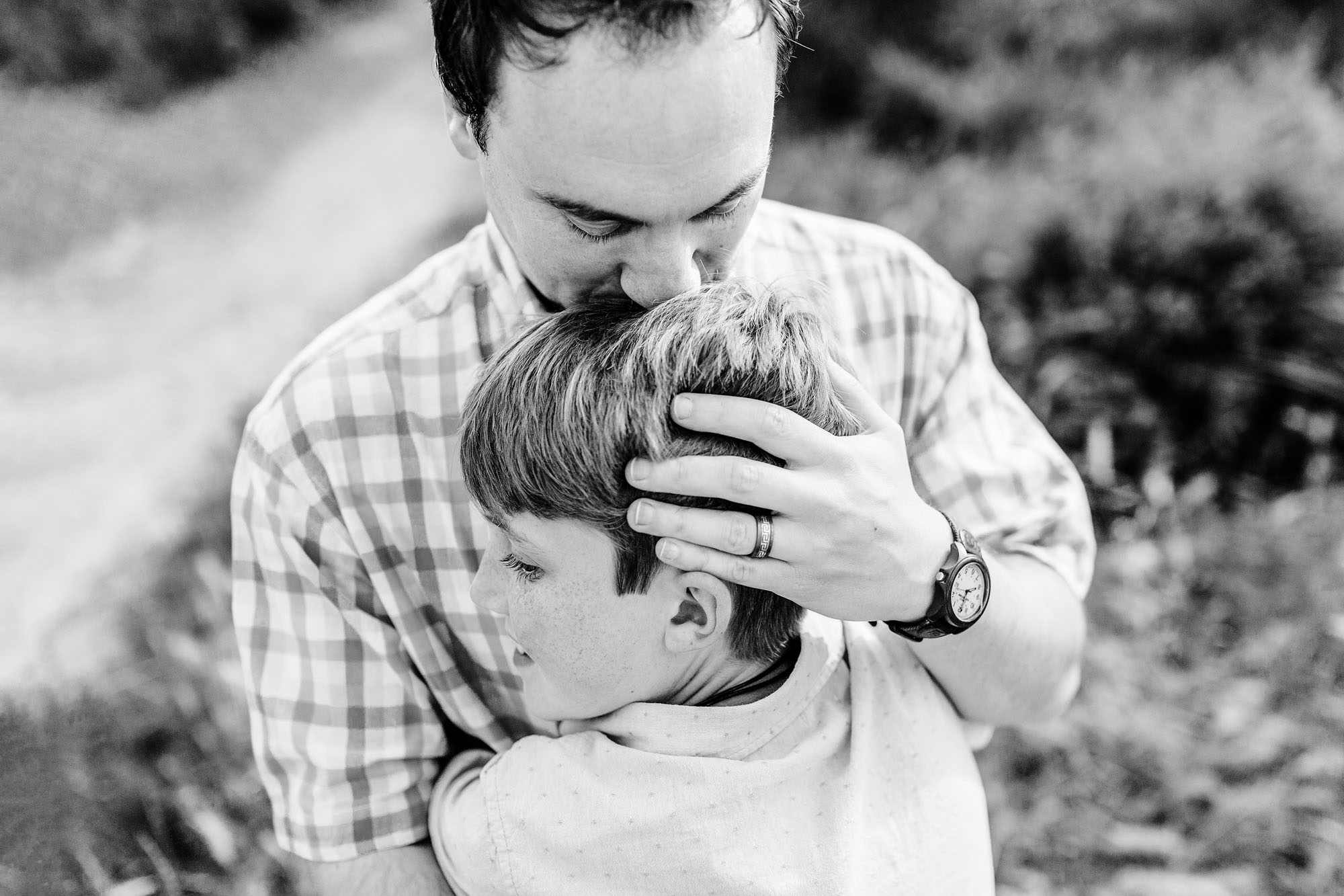 A father kisses his son and hugs him with love during a lifestyle family photo session with Amy Wright, a photographer based out of Roseville, Rocklin, and Sacramento, California.