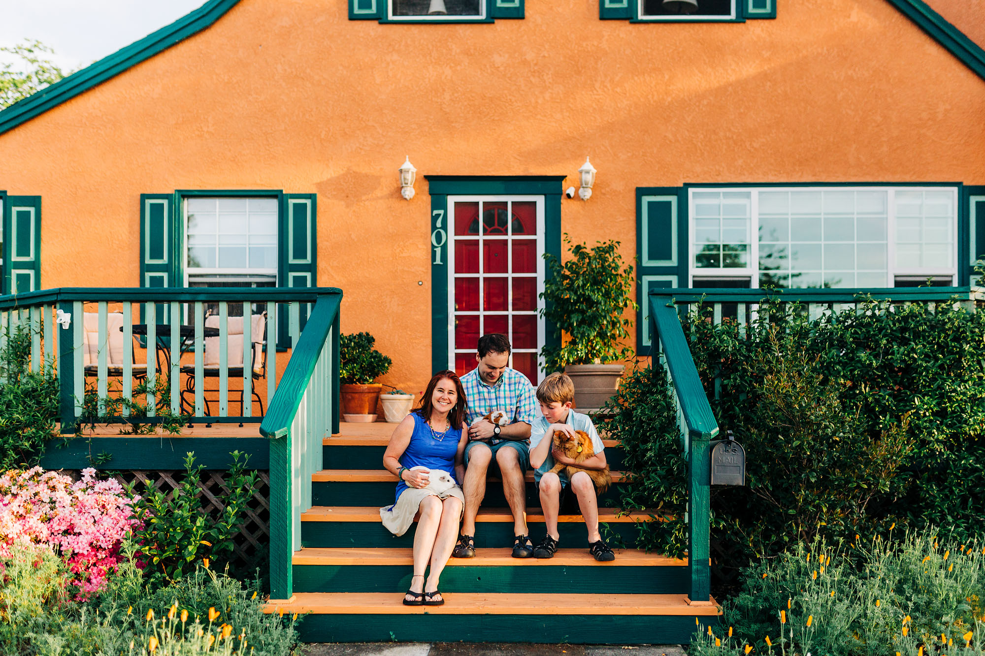 A family sits outside of their home in Roseville, California during a lifestyle photo session with Amy Wright Photography.