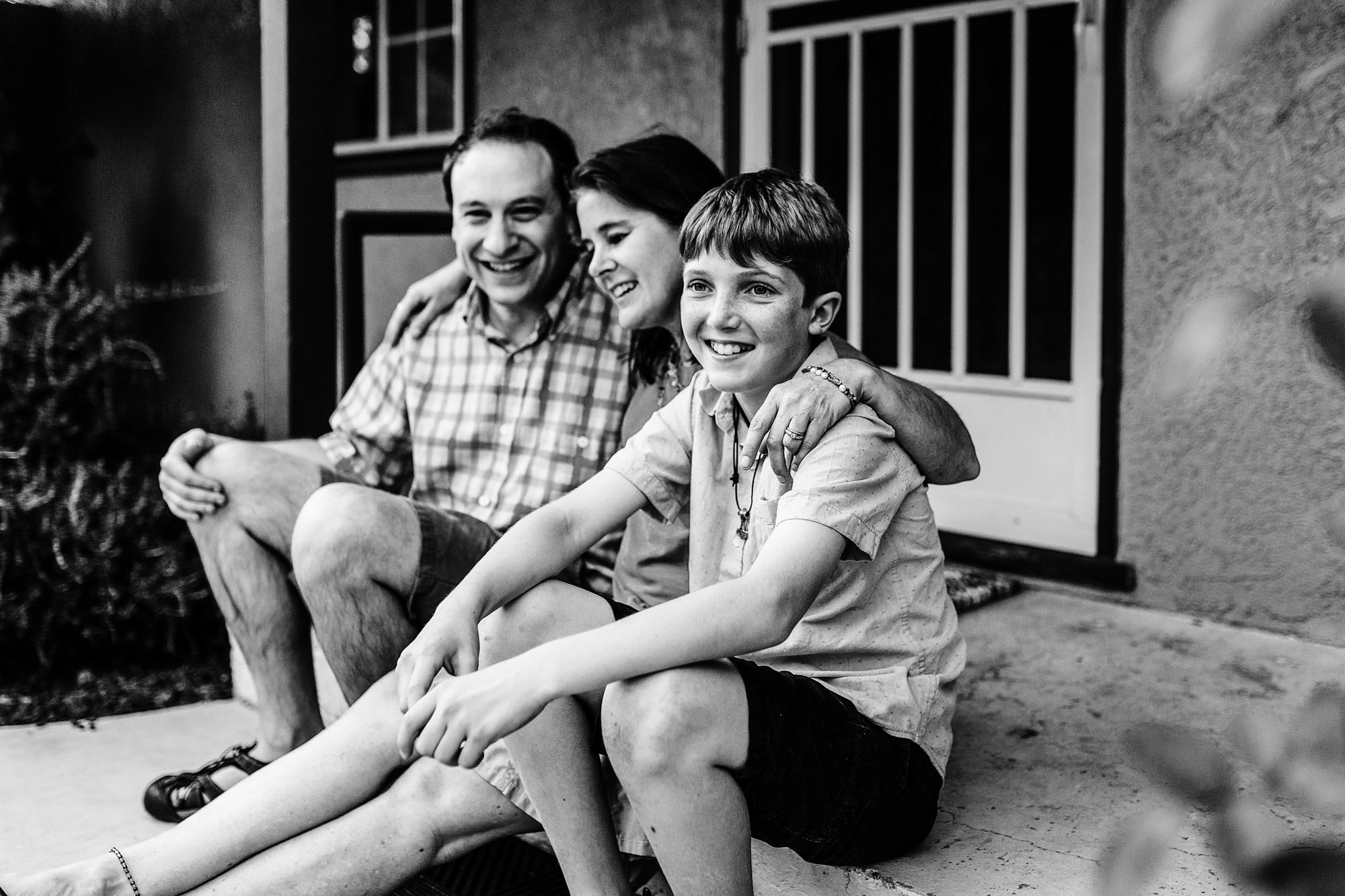 A timeless image of a son smiling with his family during a lifestyle photo session with Amy Wright, a photographer based out of Roseville, California.