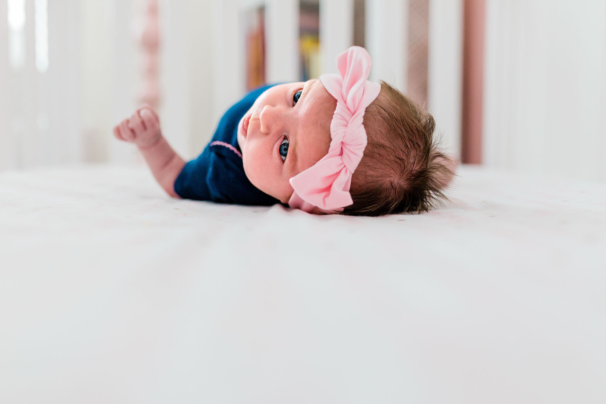 A newborn lays in her crib during an in-home lifestyle photo session with Amy Wright Photography in Sacramento, California.