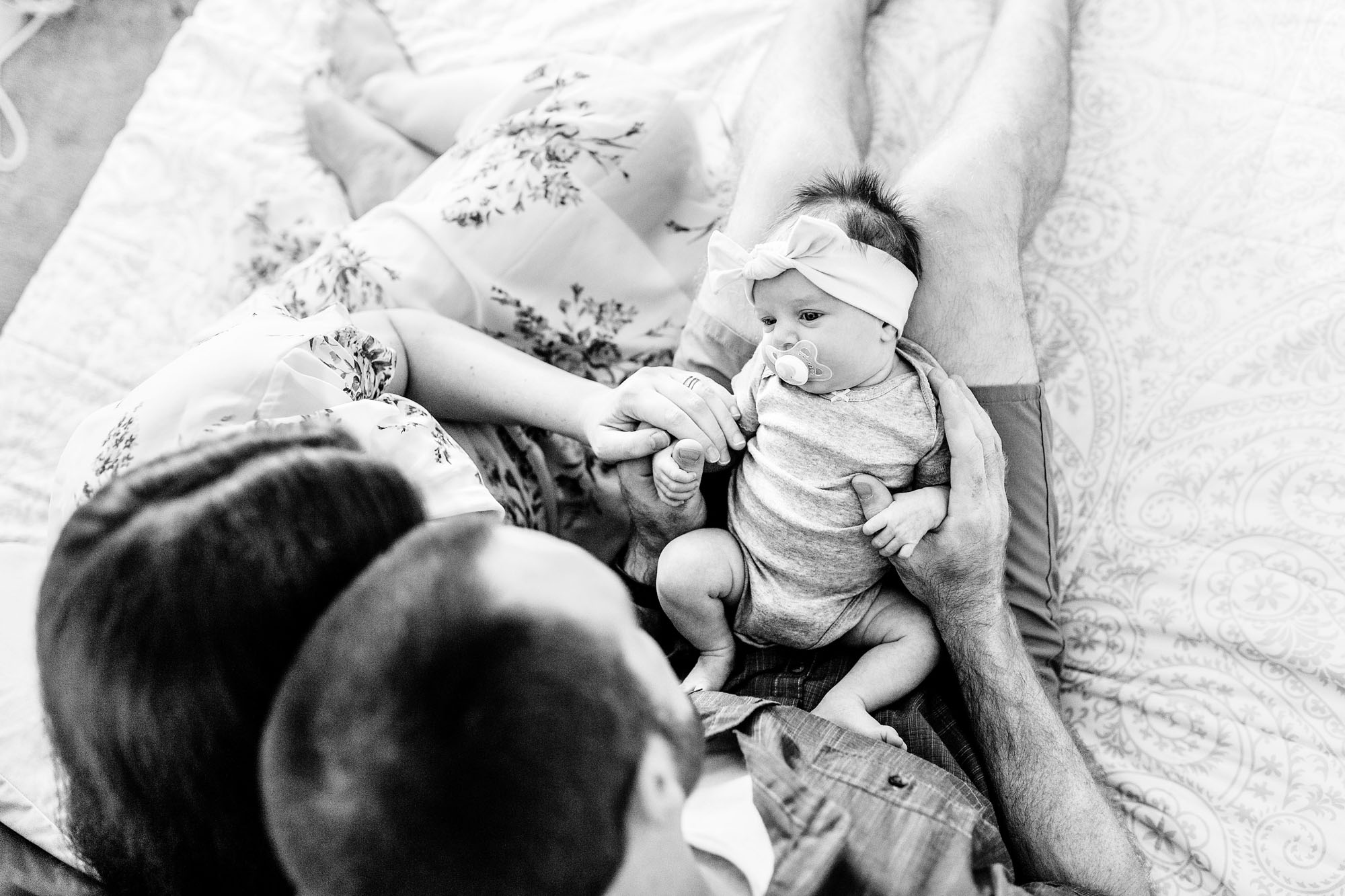 A new family of three enjoys time on the bed in their home during a newborn photo session with photographer Amy Wright in Sacramento, California.