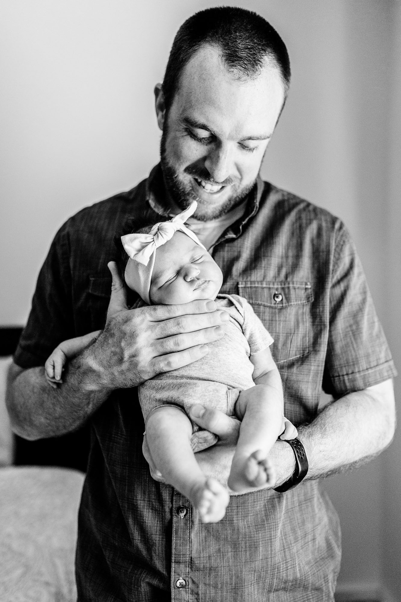 A father proudly holds his baby during an in-home newborn photo session with photographer Amy Wright, who is based out of Sacramento, Roseville, and Rocklin, California.
