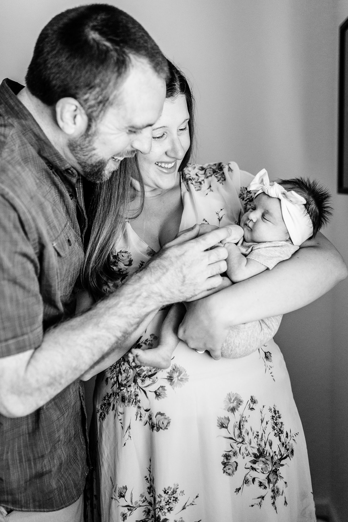 Parents lovingly hold and interact with their newborn baby during an in-home lifestyle photo shoot with photographer Amy Wright in Sacramento, California.