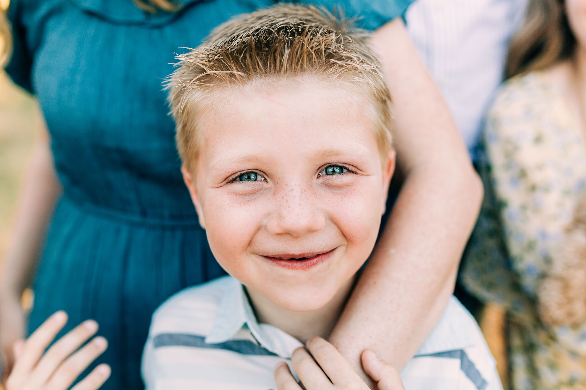 A boy smiles into the camera during family photos with Roseville family photographer Amy Wright.
