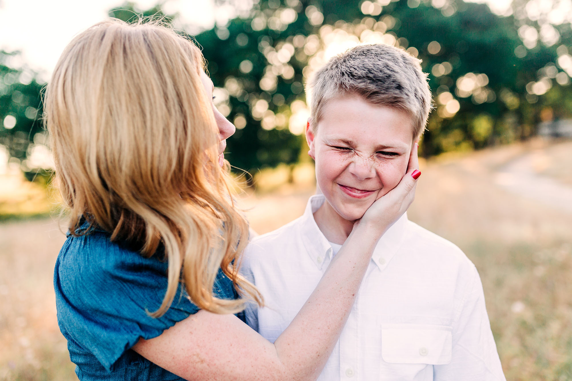 A mother cups her son's cheek during fun family pictures with lifestyle photographer Amy Wright in Roseville, California.