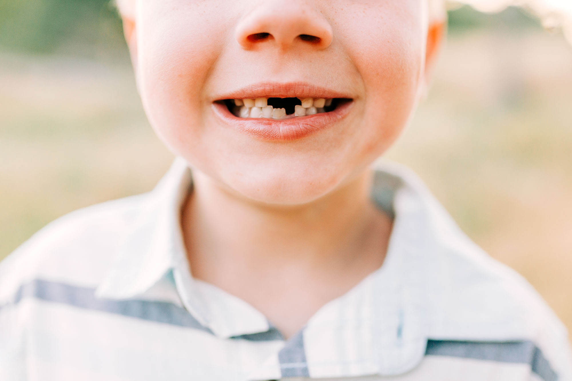 A detailed portrait shot is taken of a child during a family photo session with lifestyle photographer Amy Wright in Roseville, California.